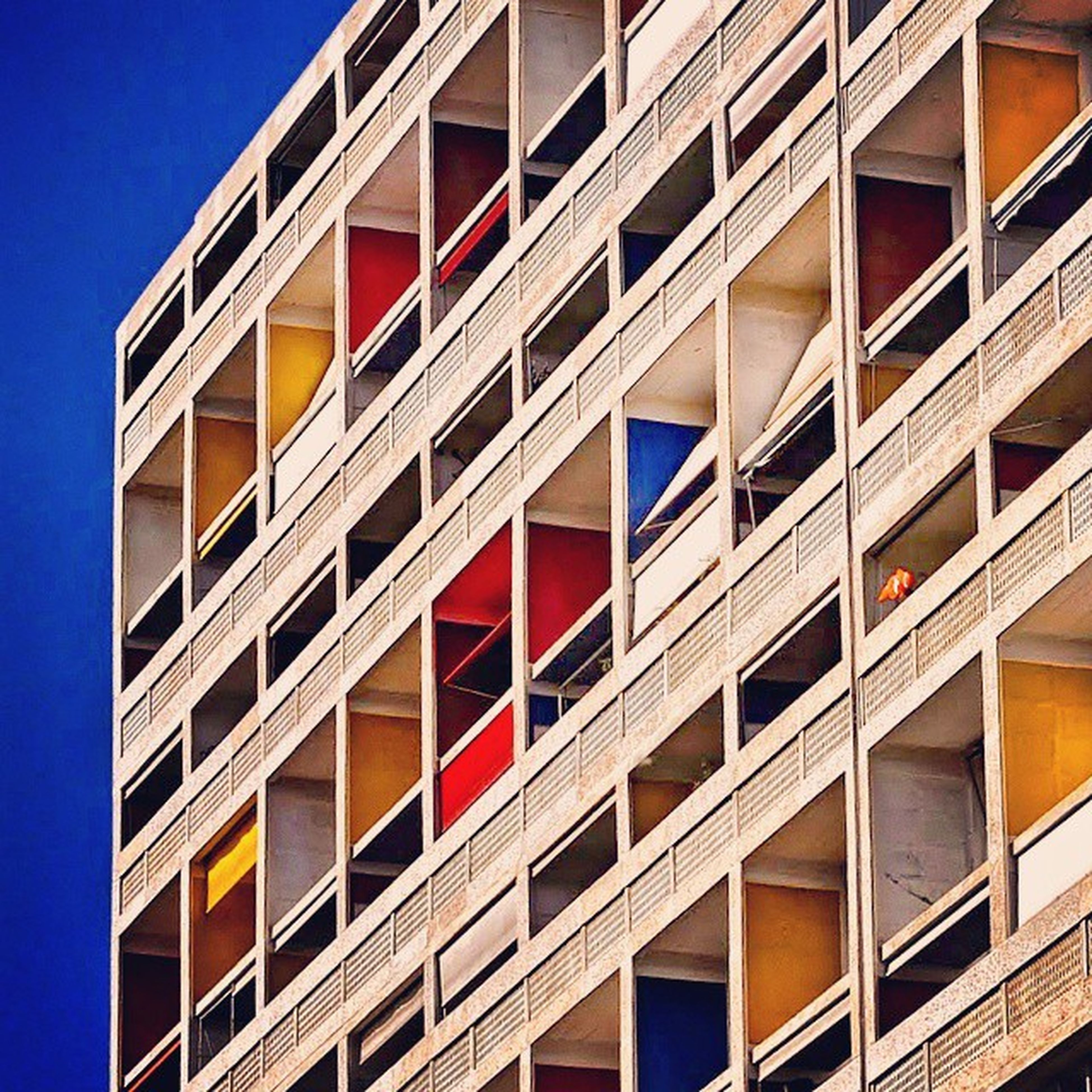architecture, building exterior, built structure, low angle view, window, building, clear sky, modern, city, blue, office building, repetition, residential building, residential structure, outdoors, reflection, day, apartment, glass - material, no people