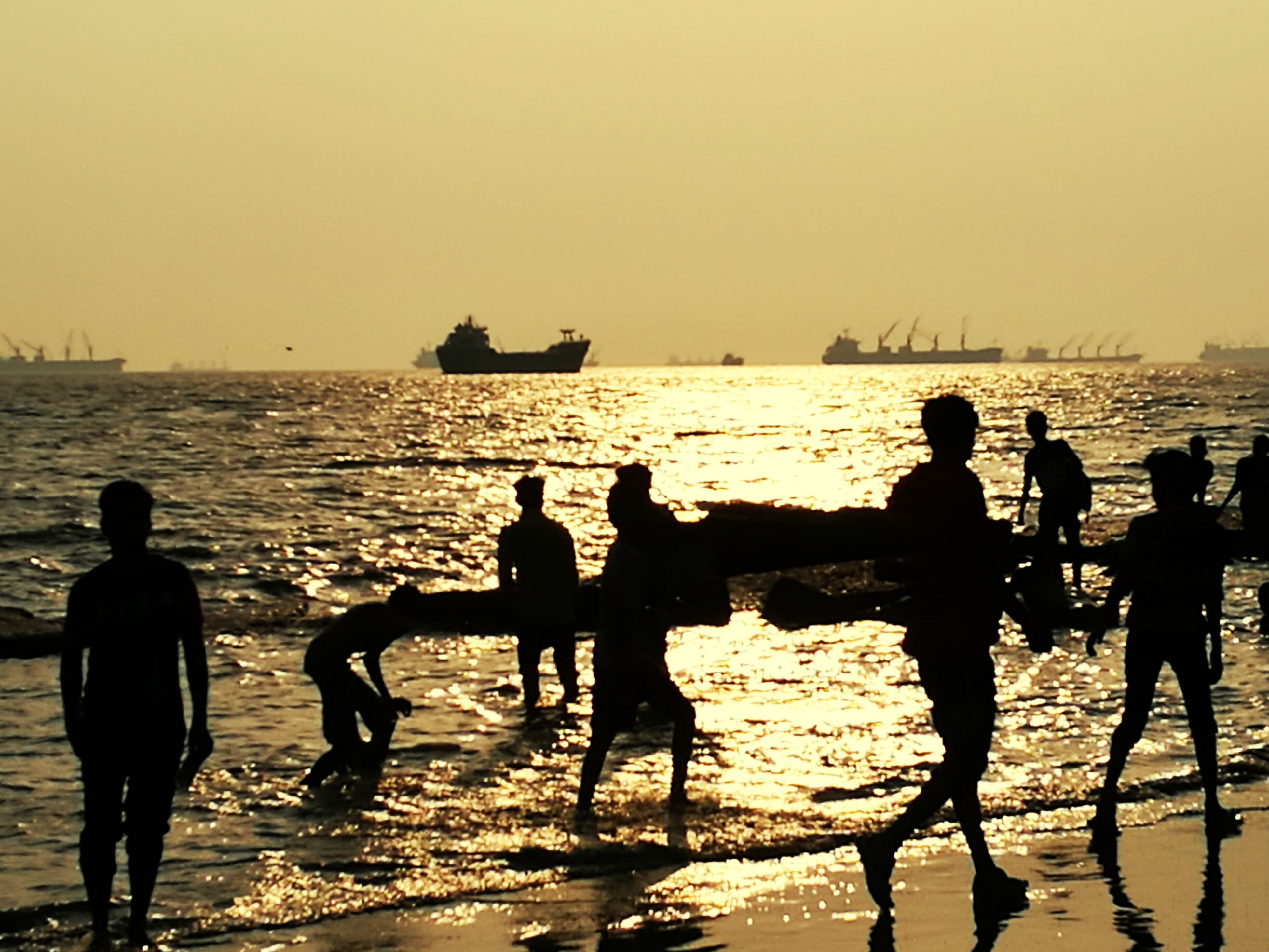 sea, water, silhouette, sunset, horizon over water, beach, sunlight, standing, nature, men, sky, real people, outdoors, scenics, medium group of people, beauty in nature, leisure activity, togetherness, cooperation, nautical vessel, lifestyles, teamwork, sport, vacations, wave, clear sky, day, people
