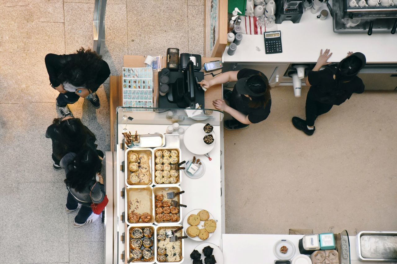 Variation Business Finance And Industry Indoors  Choice Arial View Top View Caffè Sweets Marketplace Modern People Making Food Making Sweets Cashier  Popular People And Places People At Work Standing Table Occupation Business High Angle View Adult Cooperation The Street Photographer - 2017 EyeEm Awards