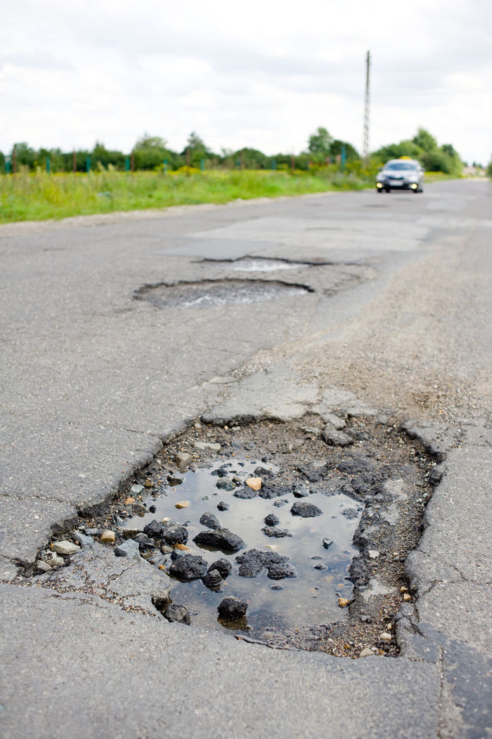 Puddle and rubbles in chuckhole in asphalt damaged road in Poland. Rain water and danger pothole detail, blurred car driving afar in vertical orientation, nobody. Asphalt Car Chuckhole Chuckholes Damaged Dilapidated Hole Holes No People Outdoors Poland Pothole Potholes Puddle Rain Road Rocks Rubble Rubbles Street Surface Vehicle Water Way Weathered
