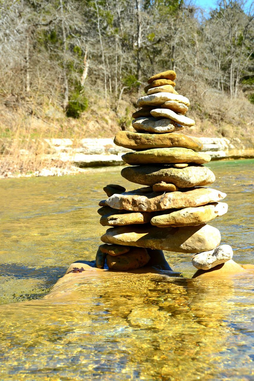 Stack Of Stones In River On Sunny Day