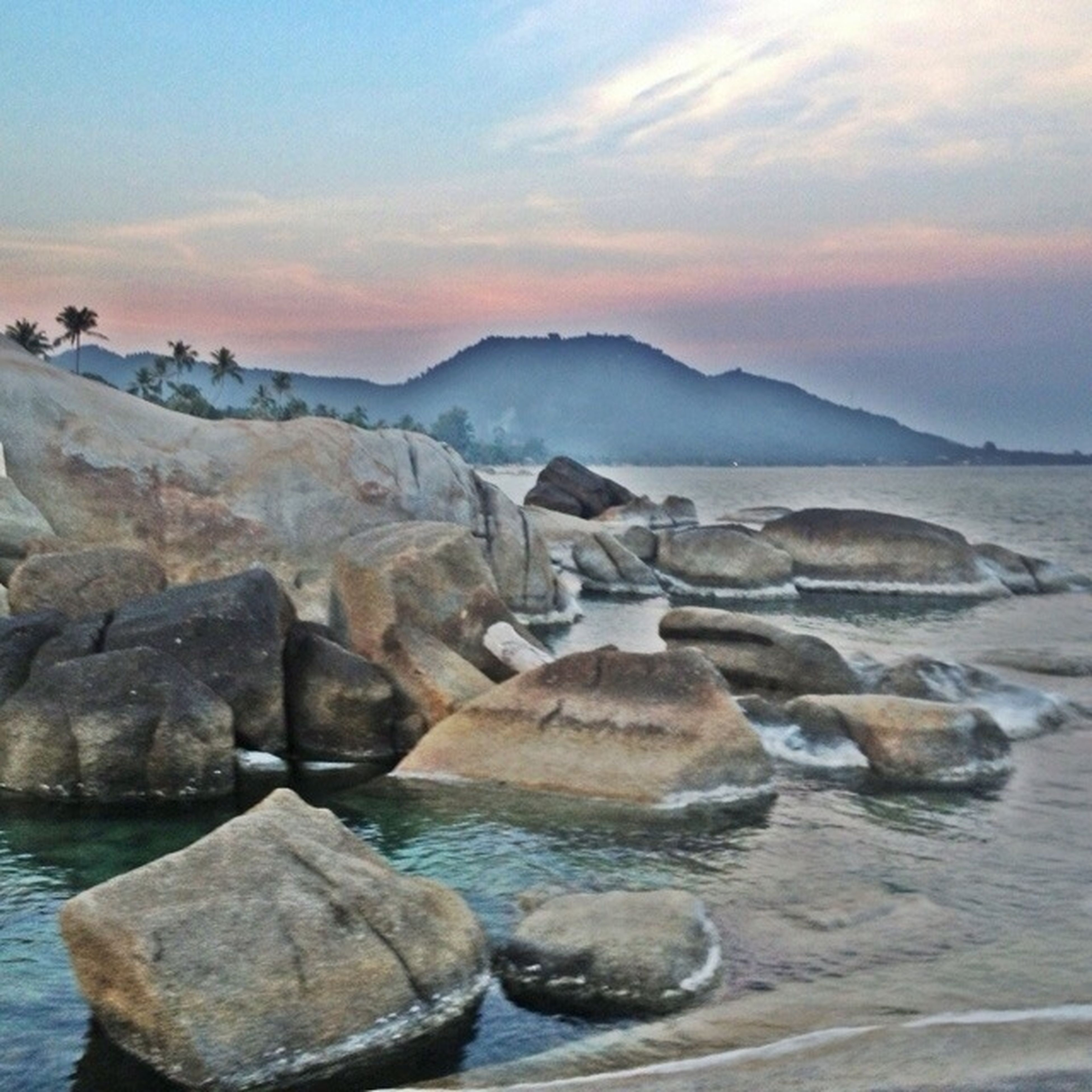 water, scenics, tranquil scene, tranquility, rock - object, beauty in nature, sky, nature, sunset, sea, waterfront, mountain, rock formation, idyllic, rock, cloud - sky, lake, non-urban scene, reflection, rippled