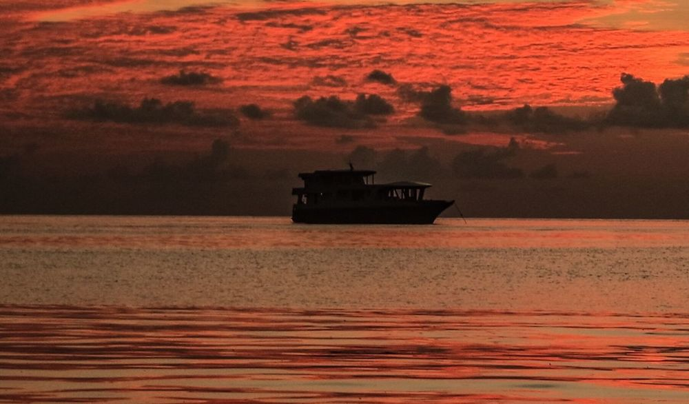 Nautical Vessel Sunset Transportation Water Sea Boat Mode Of Transport Nature Calm Dramatic Sky Scenics Silhouette Waterfront Calm Tranquility Orange Color Tranquil Scene Beauty In Nature Nature Ocean Journey Romantic Sky Sky