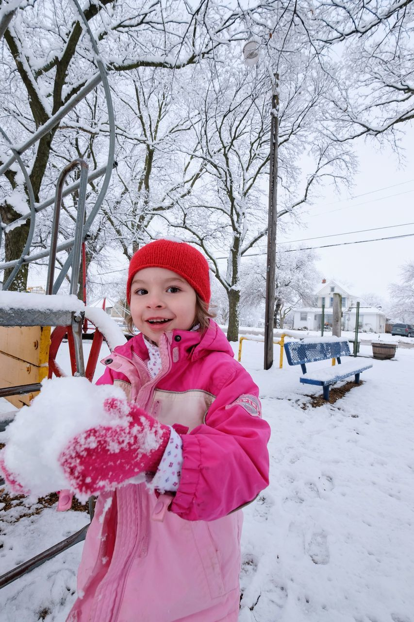 Portrait Of Happy Girl Playing With Snow By Bench