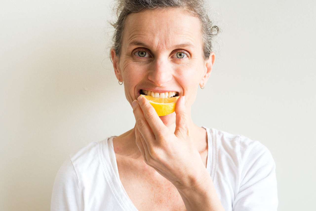 Middle aged woman biting into lemon Adult Adults Only Close-up Eating Food Food And Drink Freshness Front View Fruit Gray Background Happiness Headshot Healthy Eating Healthy Lifestyle Human Body Part Indoors  Lemon Looking At Camera Mature Adult One Person People Portrait SLICE Studio Shot Woman