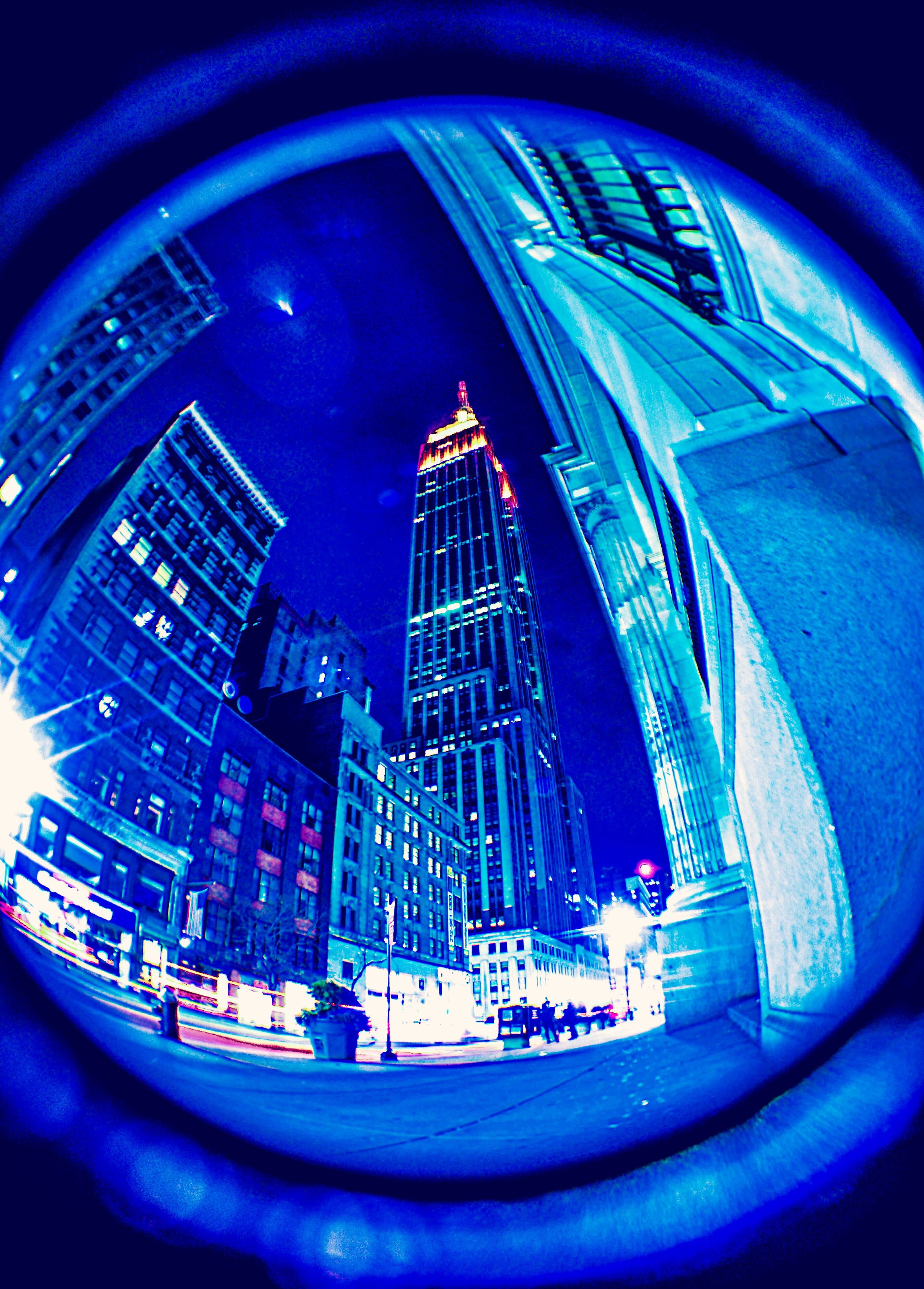 architecture, built structure, building exterior, city, mode of transport, transportation, blue, low angle view, travel, modern, fish-eye lens, car, glass - material, tower, reflection, capital cities, land vehicle, building, travel destinations, circle