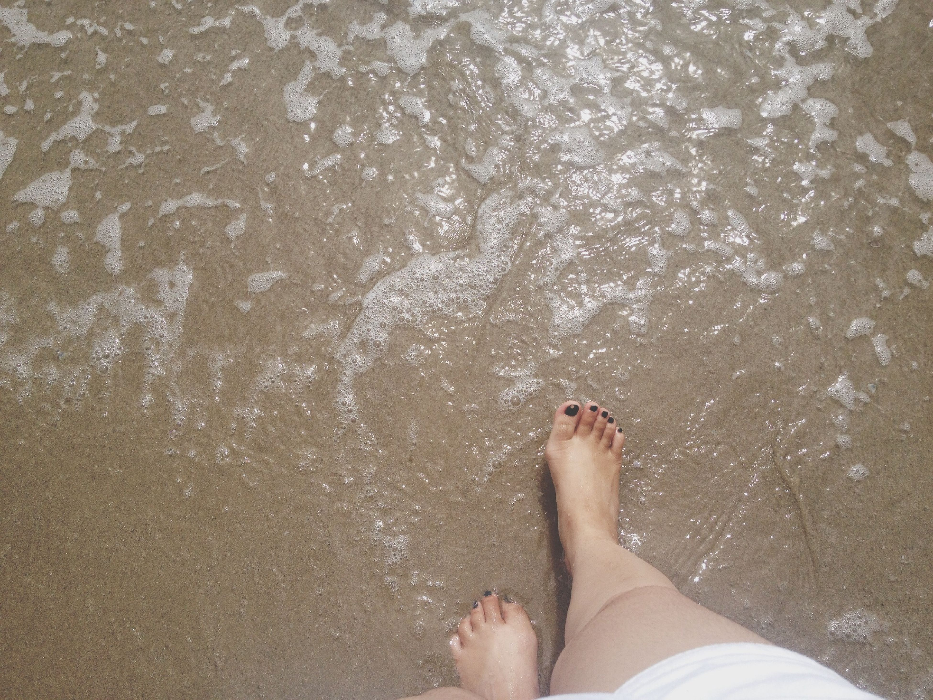 low section, person, water, personal perspective, barefoot, human foot, beach, high angle view, lifestyles, leisure activity, sand, sea, shore, standing, wet, surf