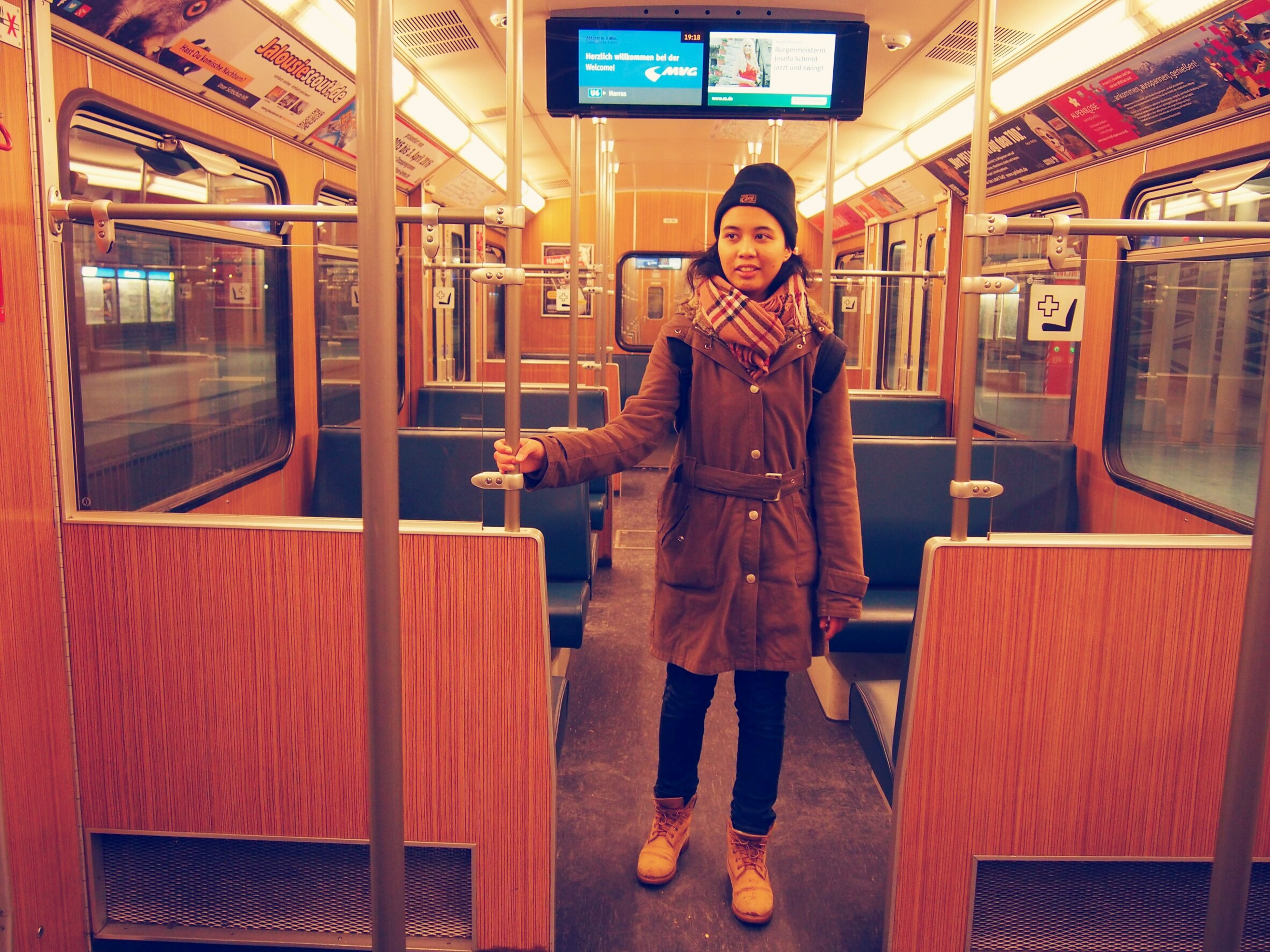 real people, public transportation, front view, looking at camera, train - vehicle, standing, lifestyles, full length, one person, portrait, young adult, transportation, young women, illuminated, leisure activity, warm clothing, subway train, technology, indoors, day