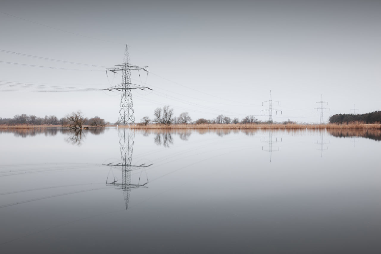 reflection of electricity pylon in winter against sky Beauty In Nature Brandenburg Cable Cold Temperature Copy Space Day Electricity Pylon Fine Art Havelland Landscape Landscapes Long Exposure Muted Colors Nature No People Outdoors Philipp Dase Reflection Sky Standing Water Symmetry Tranquility Tree Water Winter