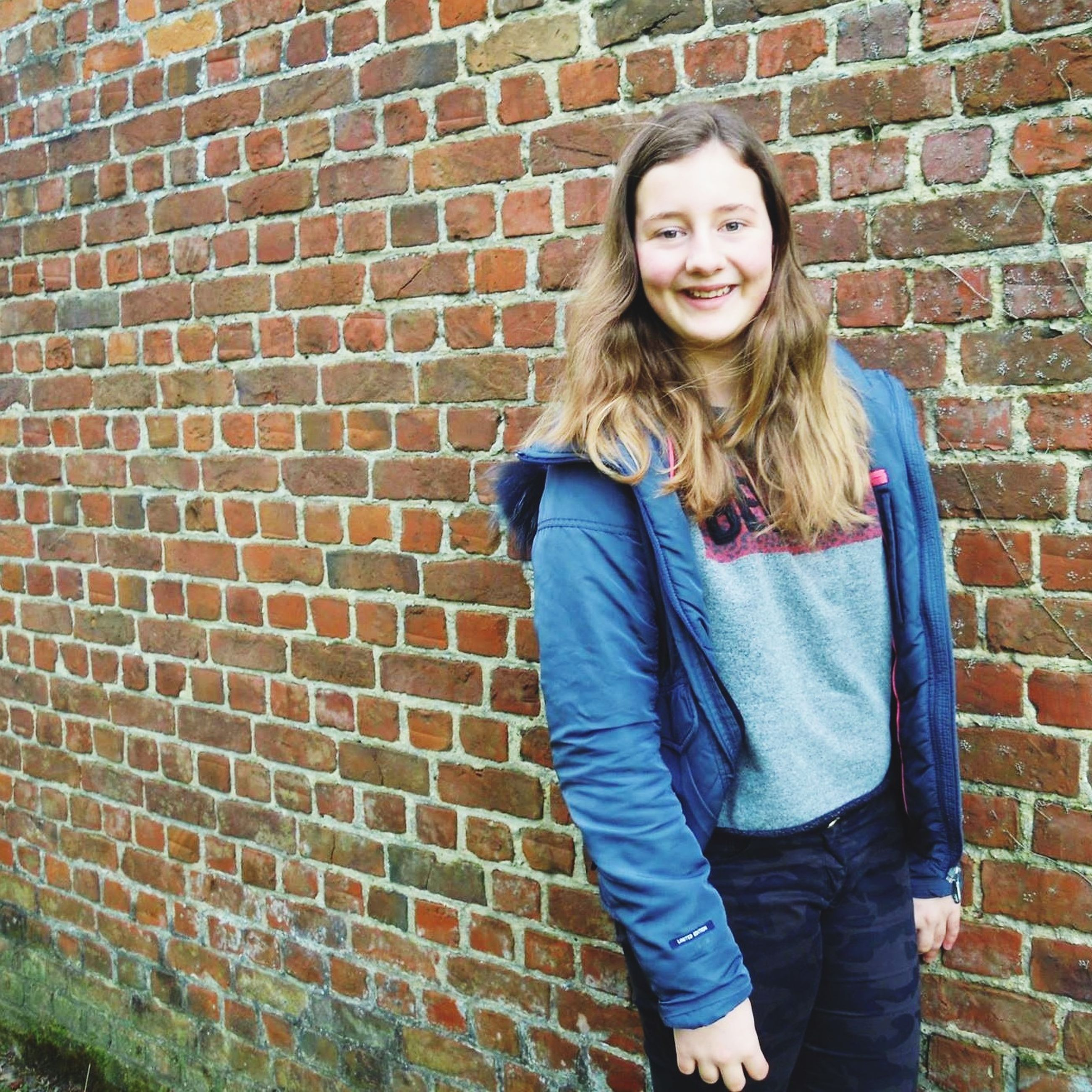 young adult, person, young women, portrait, looking at camera, casual clothing, lifestyles, front view, long hair, smiling, standing, brick wall, leisure activity, three quarter length, happiness, medium-length hair