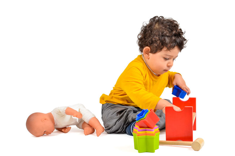 Boy is playing and learning with didactic toys Child Childhood Children Only Curly Hair Didactic Human Body Part Lifestyles Mulatto  Multi Colored One Person People Playing Studio Shot Toys White Background