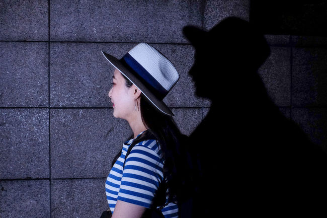 "I will Follow You . ""The Hardest light cast the darkest shadow"". Hat KLCC Tower KLCC Twin Towers Lady Malaysia Shadows & Lights Street Art Street Fashion Streetphotography Stripes Pattern"