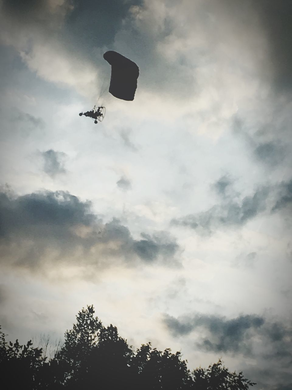 low angle view, tree, mid-air, sky, adventure, silhouette, cloud - sky, flying, outdoors, day, nature, parachute, extreme sports, sport, one person, paragliding, beauty in nature, people
