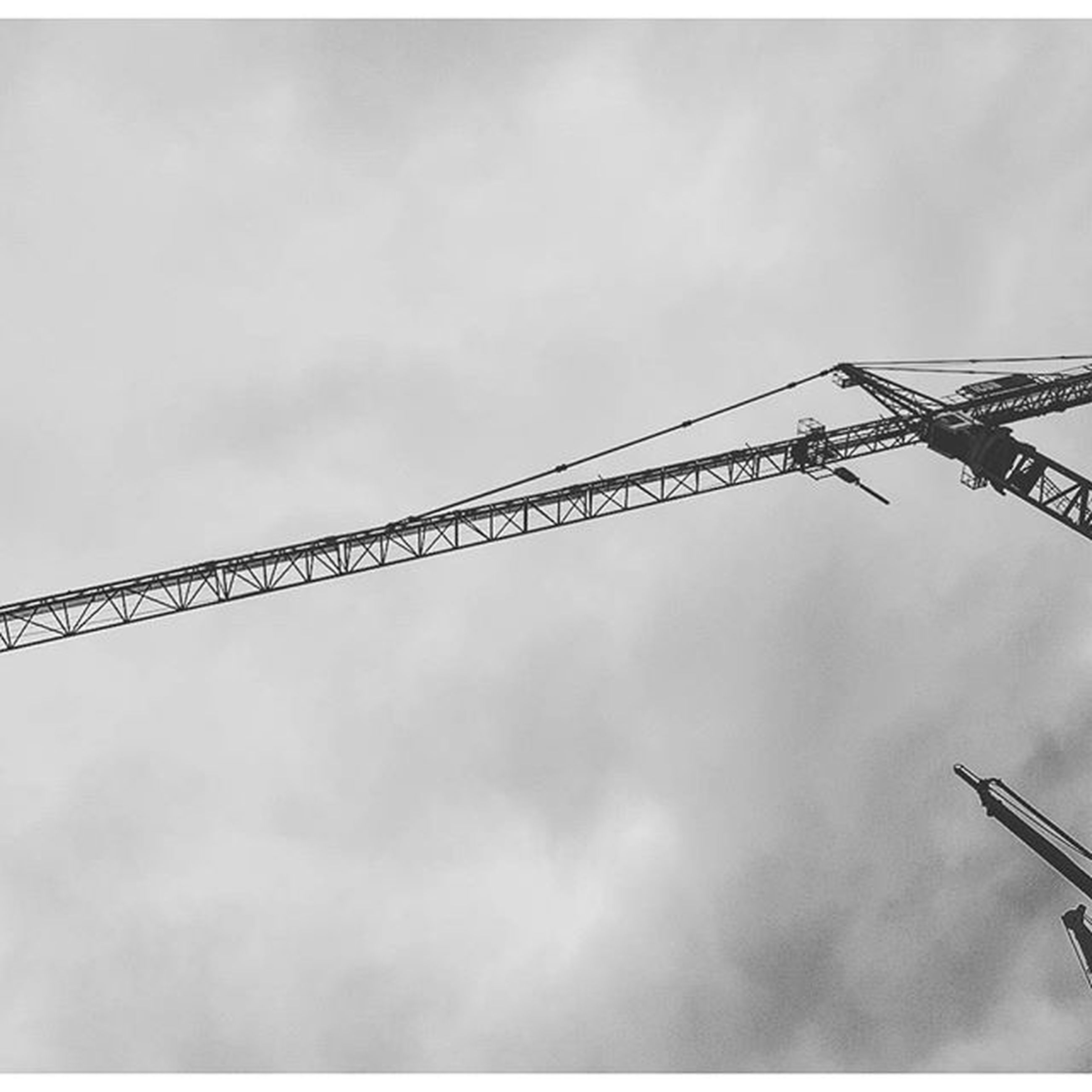 fuel and power generation, low angle view, sky, barbed wire, safety, construction site, protection, metal, connection, fence, crane - construction machinery, power supply, development, security, technology, electricity, day, construction, crane, outdoors
