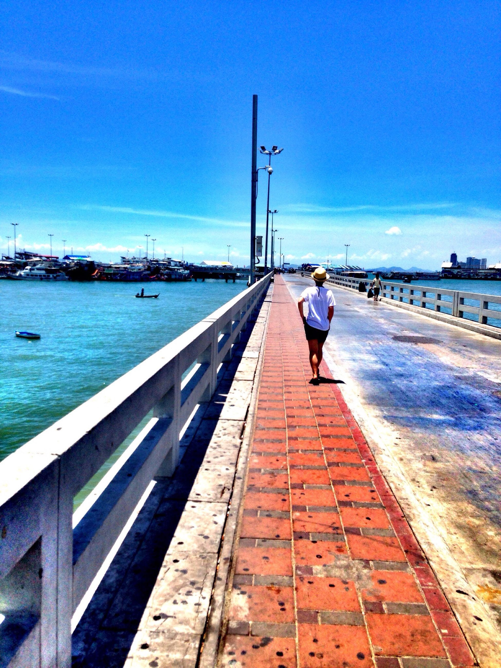 water, the way forward, sea, full length, pier, sky, rear view, railing, lifestyles, walking, leisure activity, diminishing perspective, built structure, men, blue, vanishing point, person, day