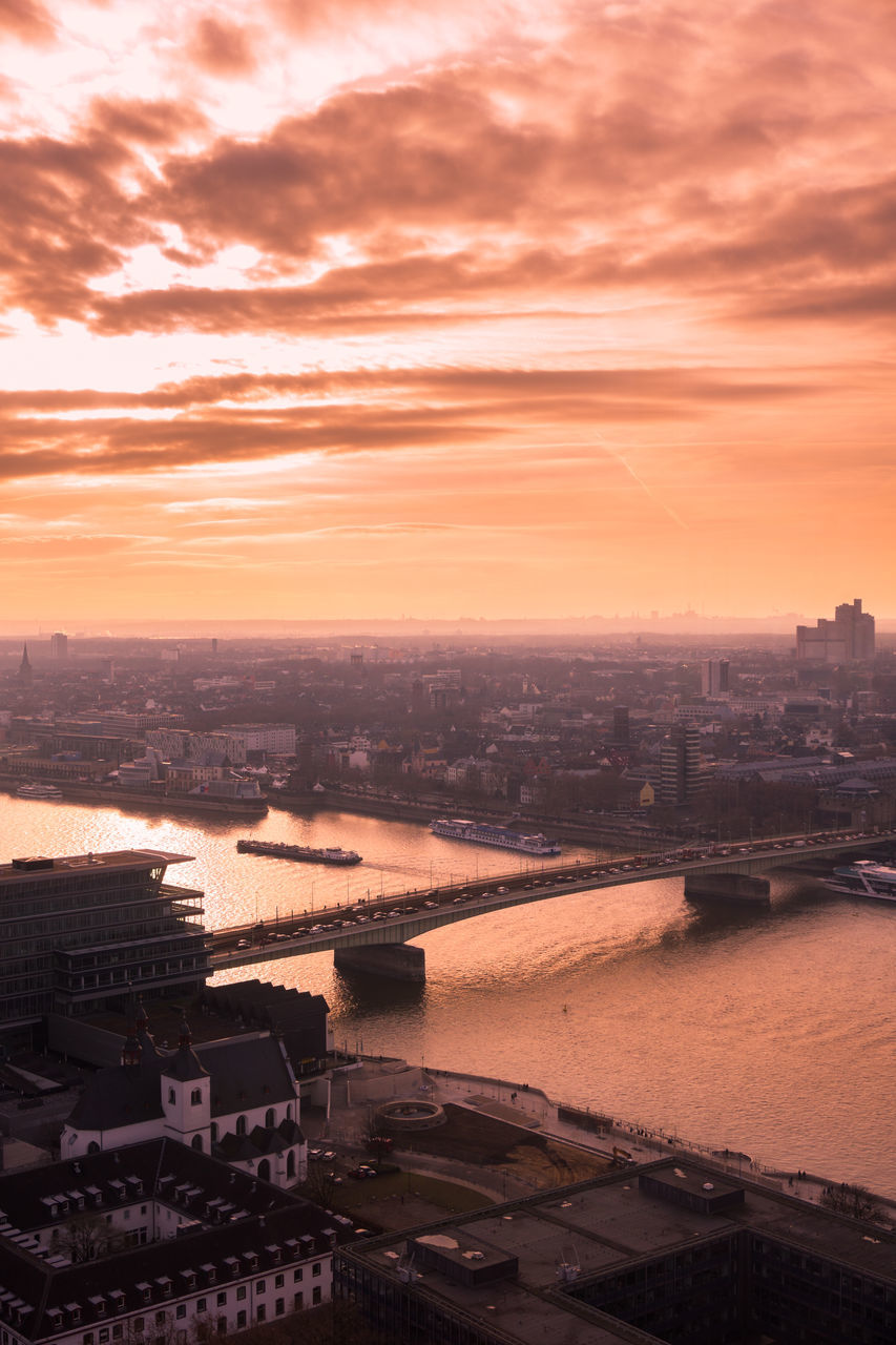 Bridge Over Rhine River Against Cloudy Sky During Sunset In City