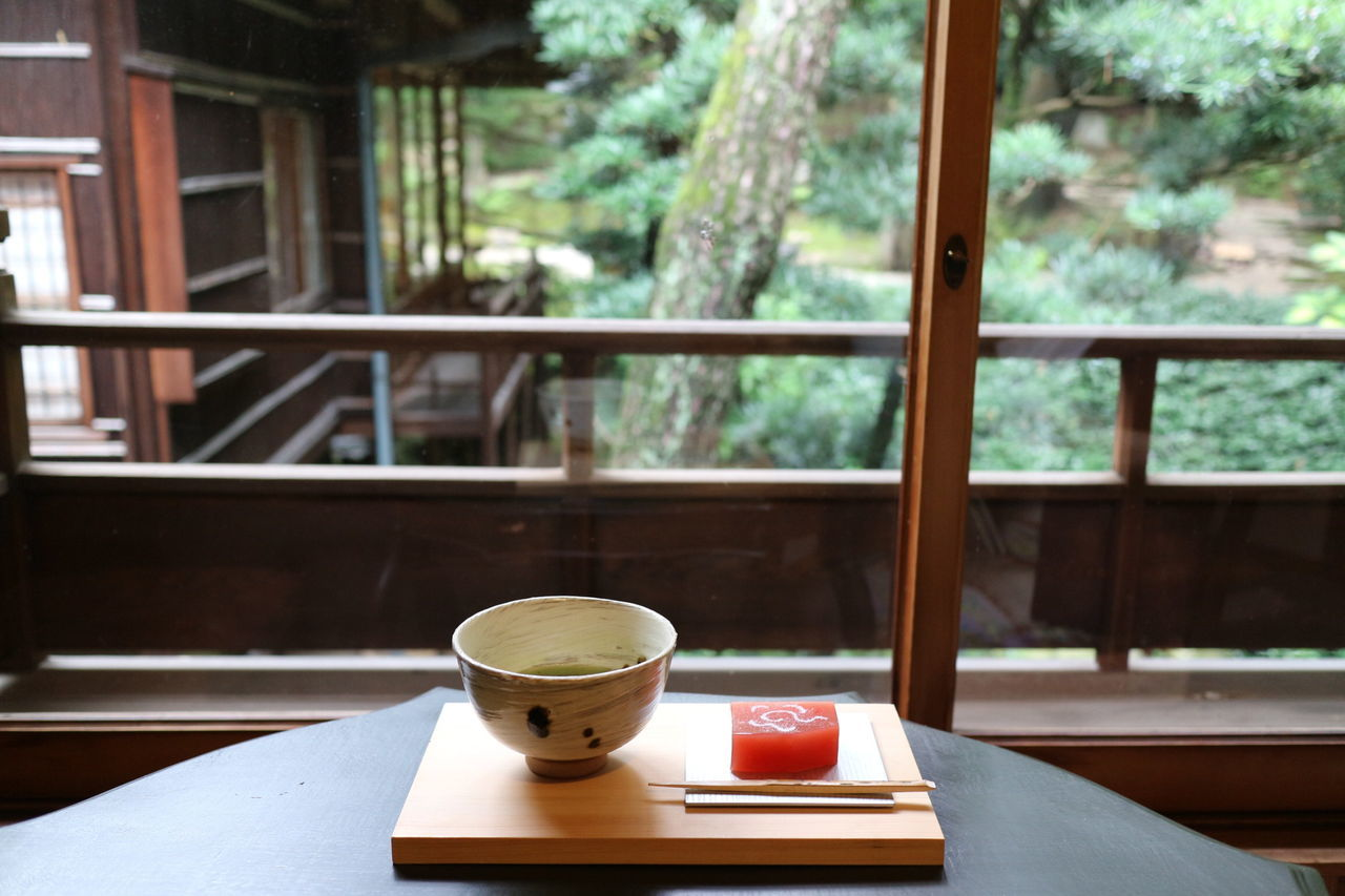 table, window, coffee cup, food and drink, drink, wood - material, refreshment, coffee - drink, indoors, focus on foreground, day, saucer, window sill, no people, tea - hot drink, book, balcony, cafe, close-up, architecture, tree, freshness