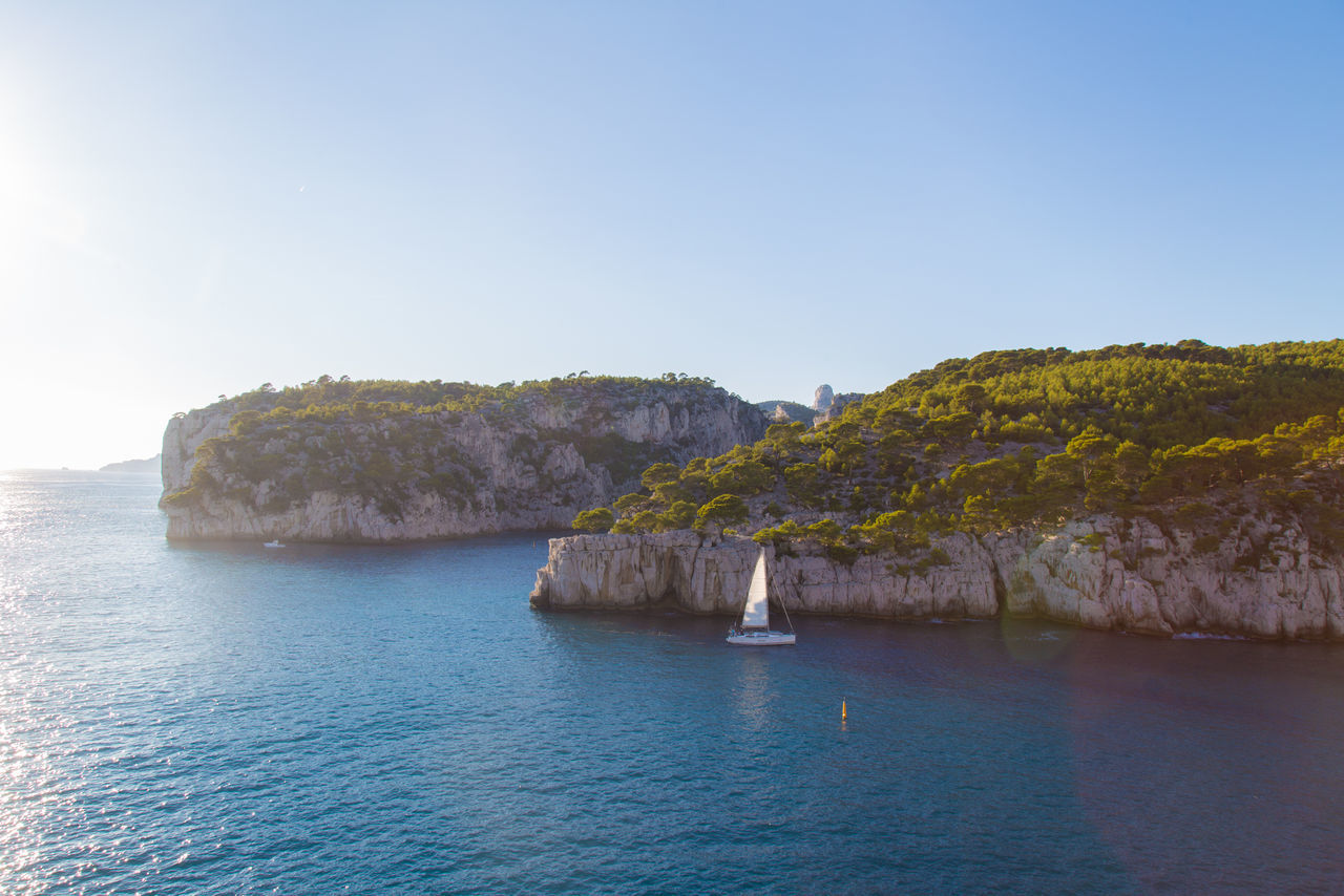 Beach Beauty In Nature Blue Blue Sea Boat Calanques  Cassis Clear Sky Day Idyllic Landscape Mediterranean  Nature Nautical Vessel No People Outdoors Sail Sailboat Scenics Sea Tourism Tranquil Scene Tranquility Tree Water