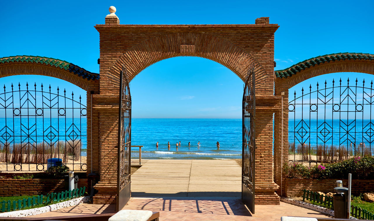 Marina d'Or beach in the Oropesa del Mar resort town. Picturesque view of a beach and Mediterranean Sea, view through the arched gates. Vacation concept. Spain Arched Gate Architecture Beach Coast Gate Horizon Over Water Idyllic Landscape Marina D'or Mediterranean Sea Oropesa Oropesa Del Mar Outdoors Picturesque Scenery Seashore Seaside SPAIN Sunny Day Tourist Resort Town Travel Destinations Vacations Walkway Waterfront