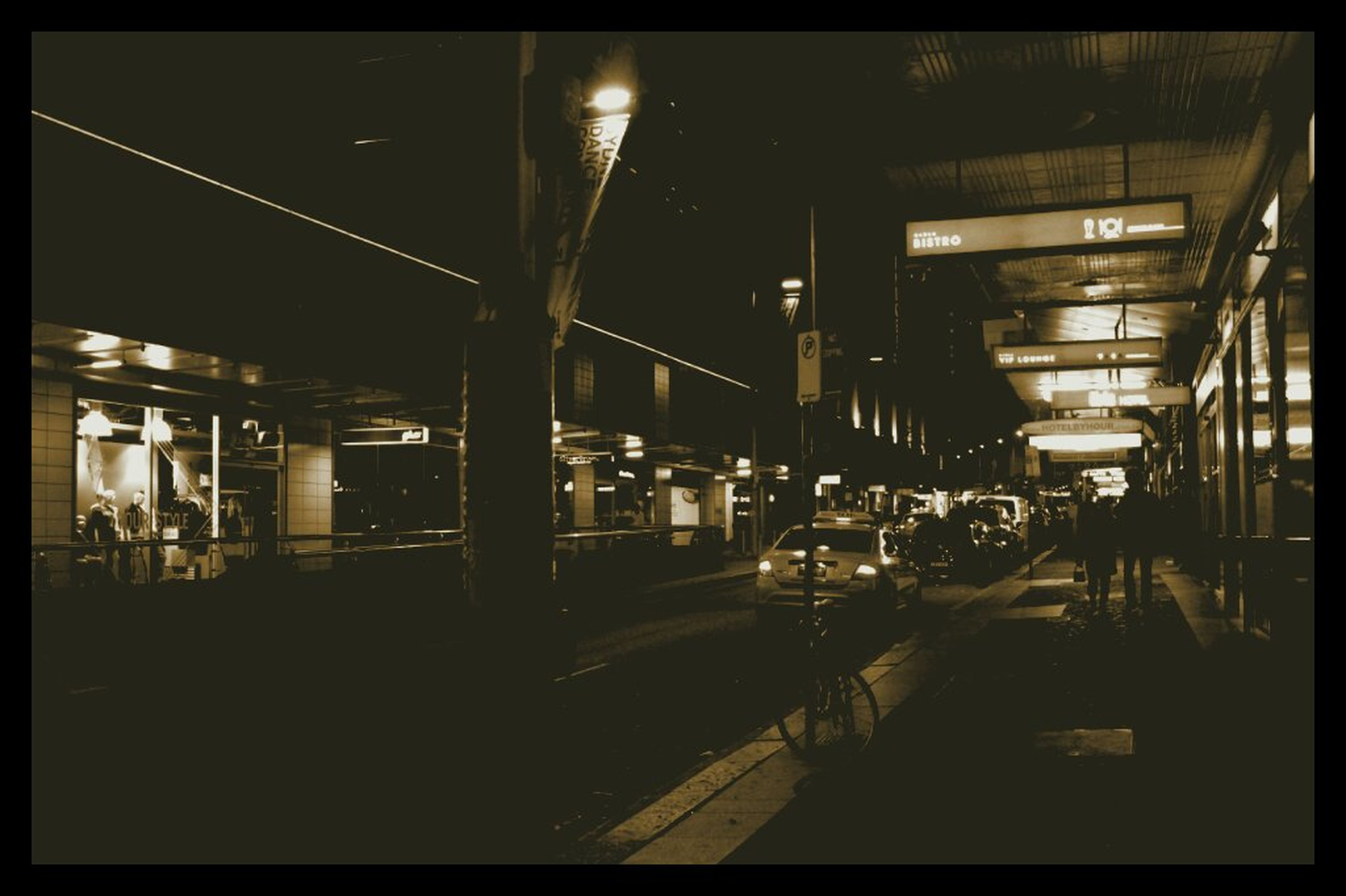 illuminated, transfer print, night, transportation, architecture, built structure, auto post production filter, city, mode of transport, building exterior, city life, public transportation, lighting equipment, street, land vehicle, railroad station, incidental people, railroad station platform, street light, car