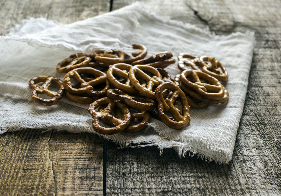 Heap of fresh Wheat salt pretzels on hessian linen fabric cloth and wooden table Close-up Cloth Fabric Focus On Foreground Fresh Group Of Objects Heap Hessian High Angle View Jewelry Linen Message No People Pearl Pretzels Salt Sea Table Text Tied Knot Traditional Culture Wave Western Script Wheat Wooden