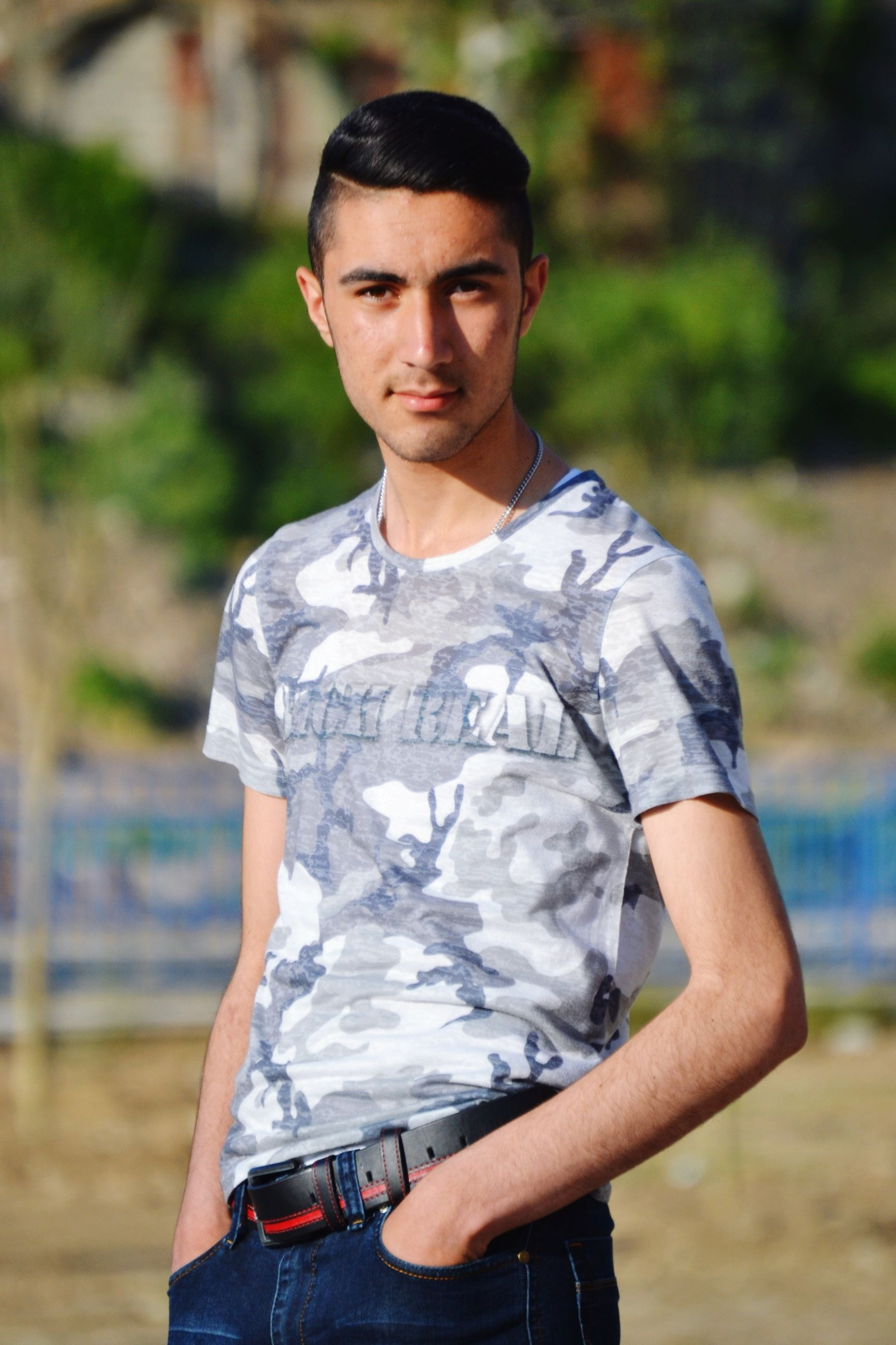 lifestyles, focus on foreground, casual clothing, leisure activity, young adult, person, looking at camera, portrait, young men, front view, standing, three quarter length, waist up, sunglasses, smiling, holding, t-shirt