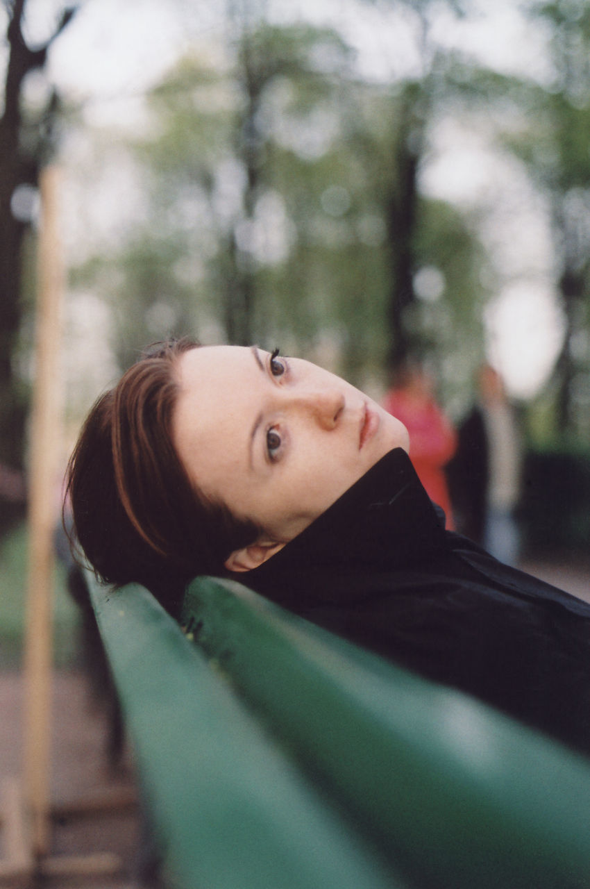 Thoughtful Woman Reclining On Bench At Park