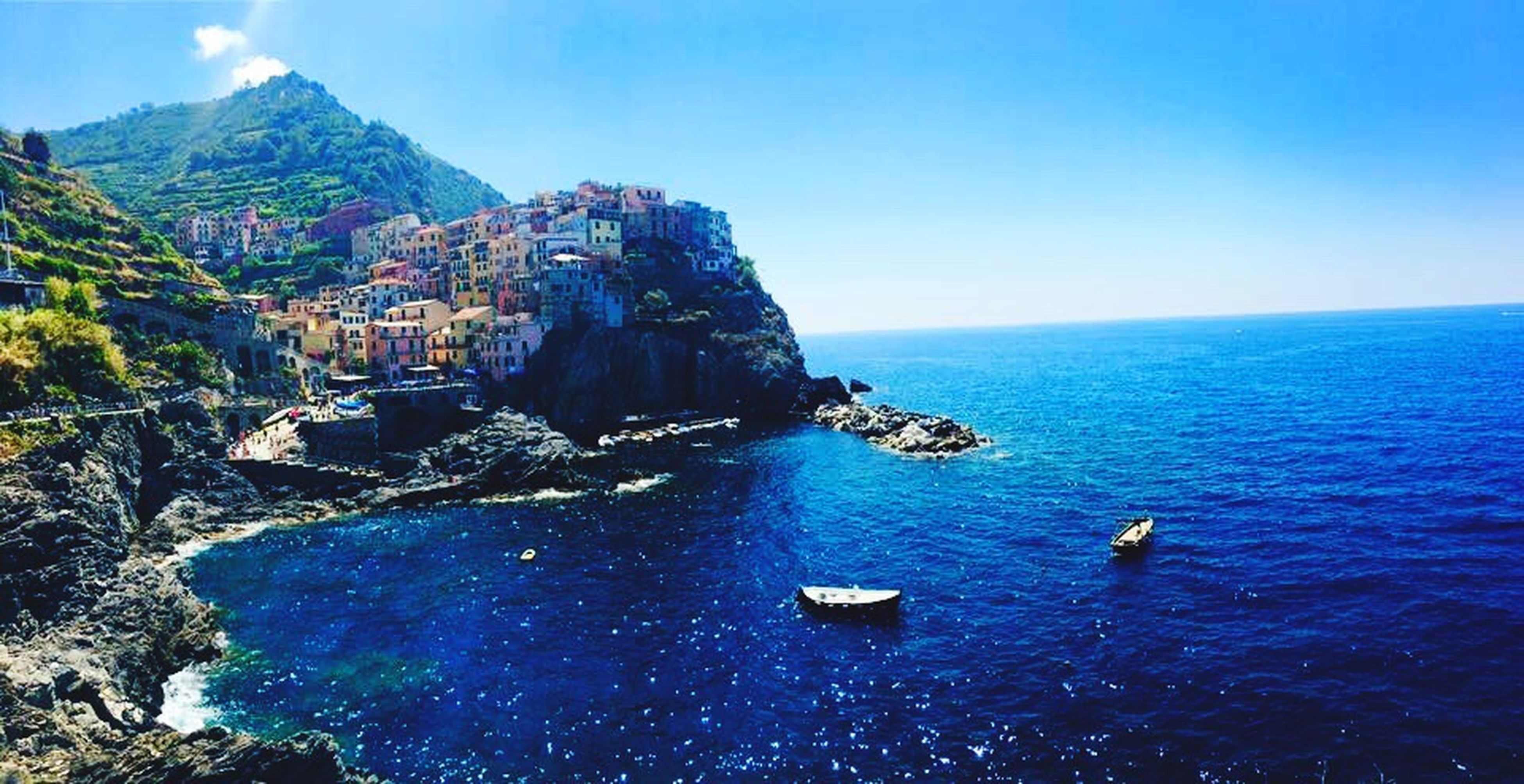 blue, water, sea, nautical vessel, built structure, architecture, clear sky, high angle view, tranquil scene, scenics, building exterior, cliff, beauty in nature, nature, tranquility, rippled, rock formation, mountain, travel destinations, day, outdoors, town, waterfront, tourism, sky, coastline, famous place, no people