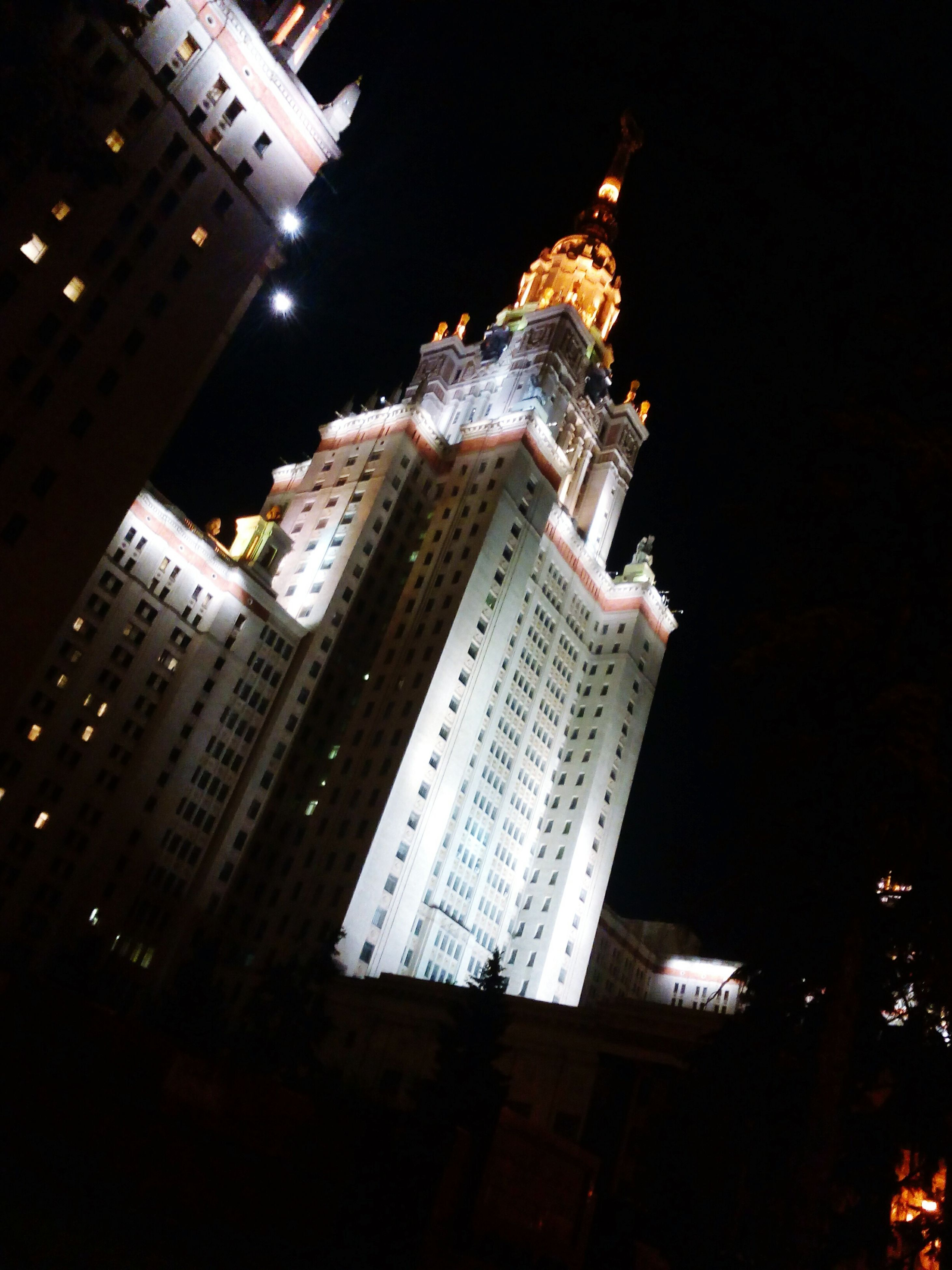 night, illuminated, building exterior, architecture, built structure, city, tall - high, low angle view, skyscraper, tower, modern, capital cities, building, office building, travel destinations, sky, city life, outdoors, famous place, tall