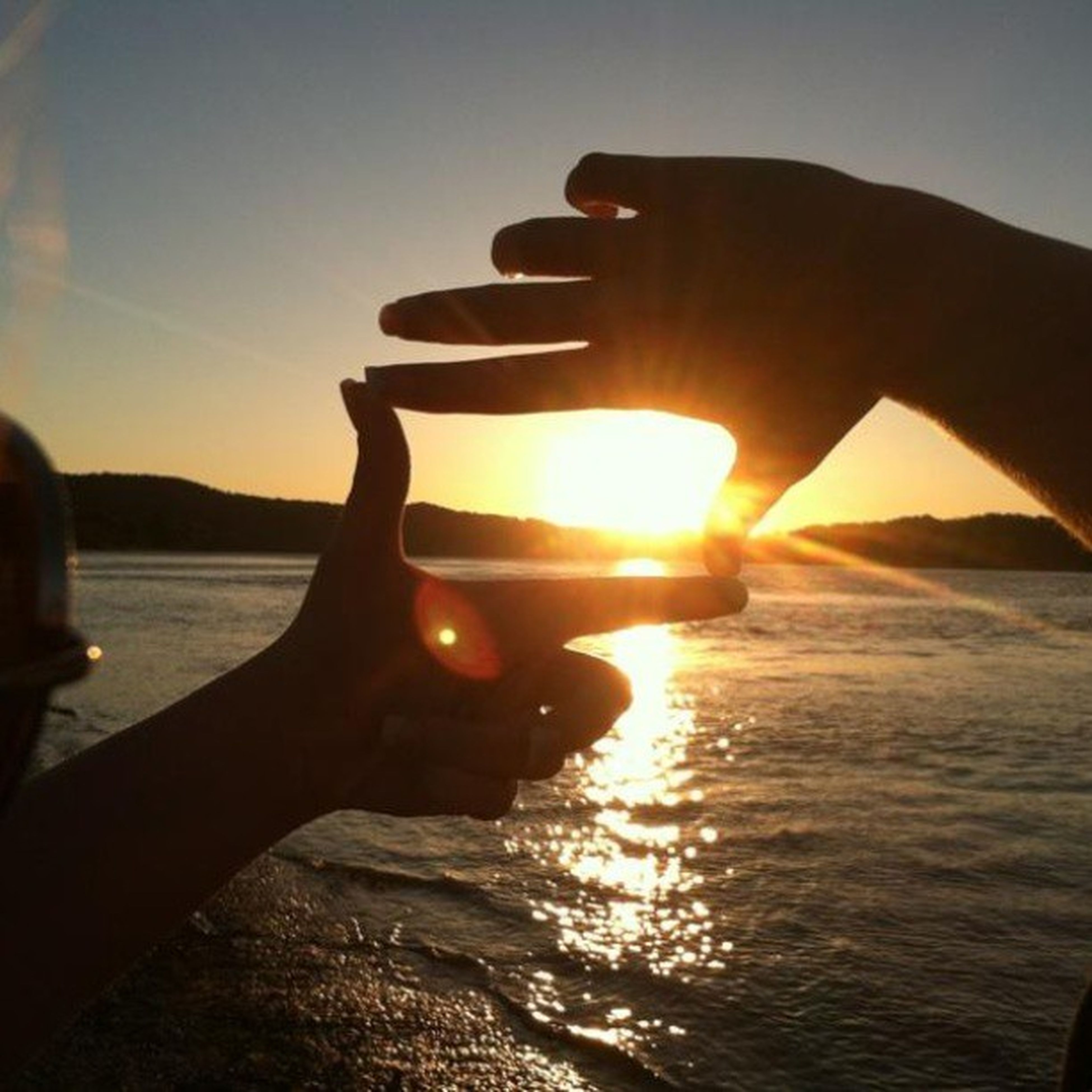 sunset, sun, water, sea, person, part of, sunlight, silhouette, sky, reflection, cropped, lens flare, sunbeam, holding, lifestyles, leisure activity, unrecognizable person