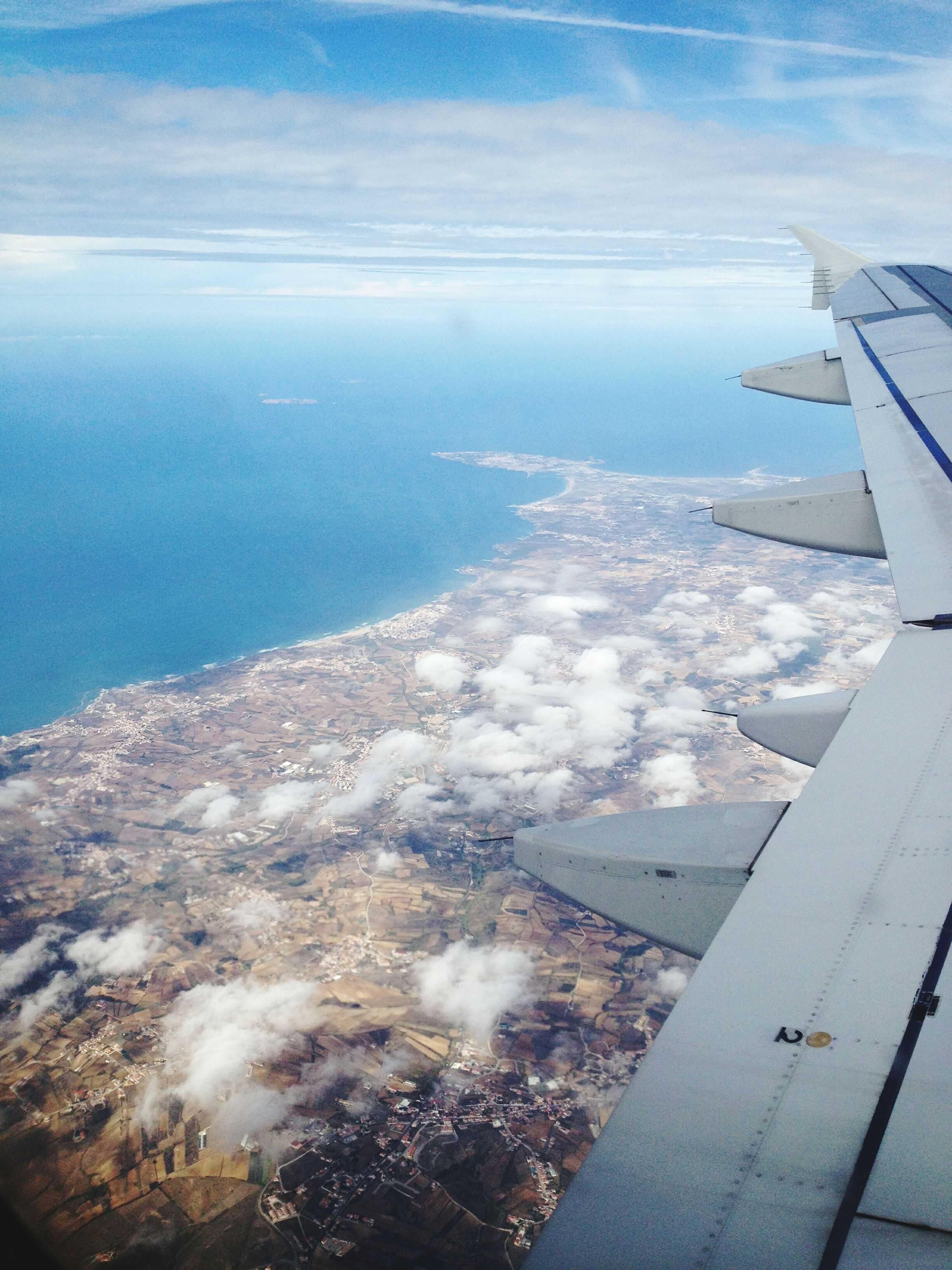 aerial view, aircraft wing, airplane, air vehicle, water, scenics, flying, transportation, beauty in nature, sky, mountain, nature, landscape, high angle view, mode of transport, blue, snow, part of, sea, cloud - sky