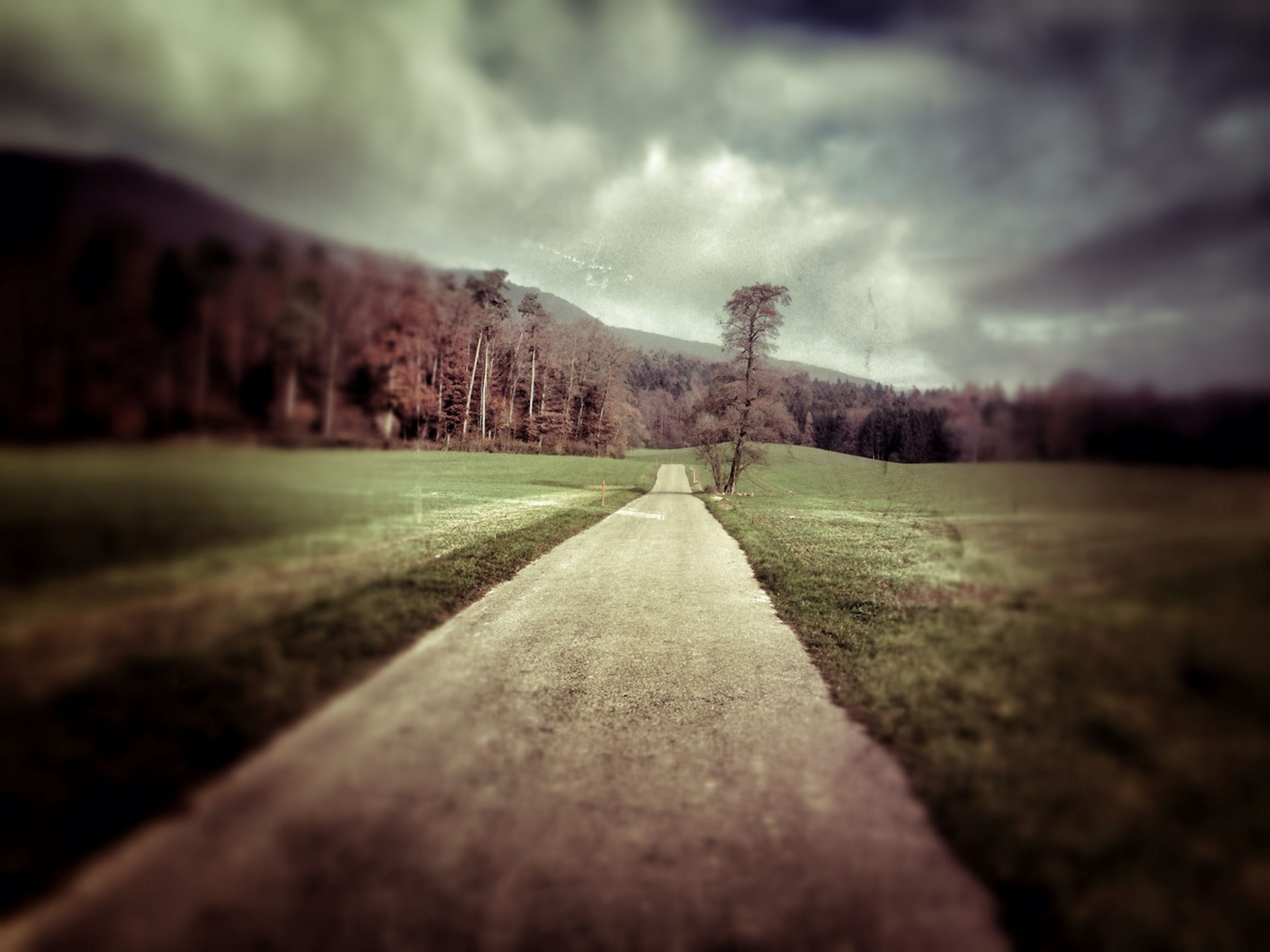 sky, landscape, the way forward, cloud - sky, tranquility, tranquil scene, cloudy, grass, field, dirt road, nature, surface level, cloud, scenics, diminishing perspective, mountain, beauty in nature, weather, selective focus, non-urban scene