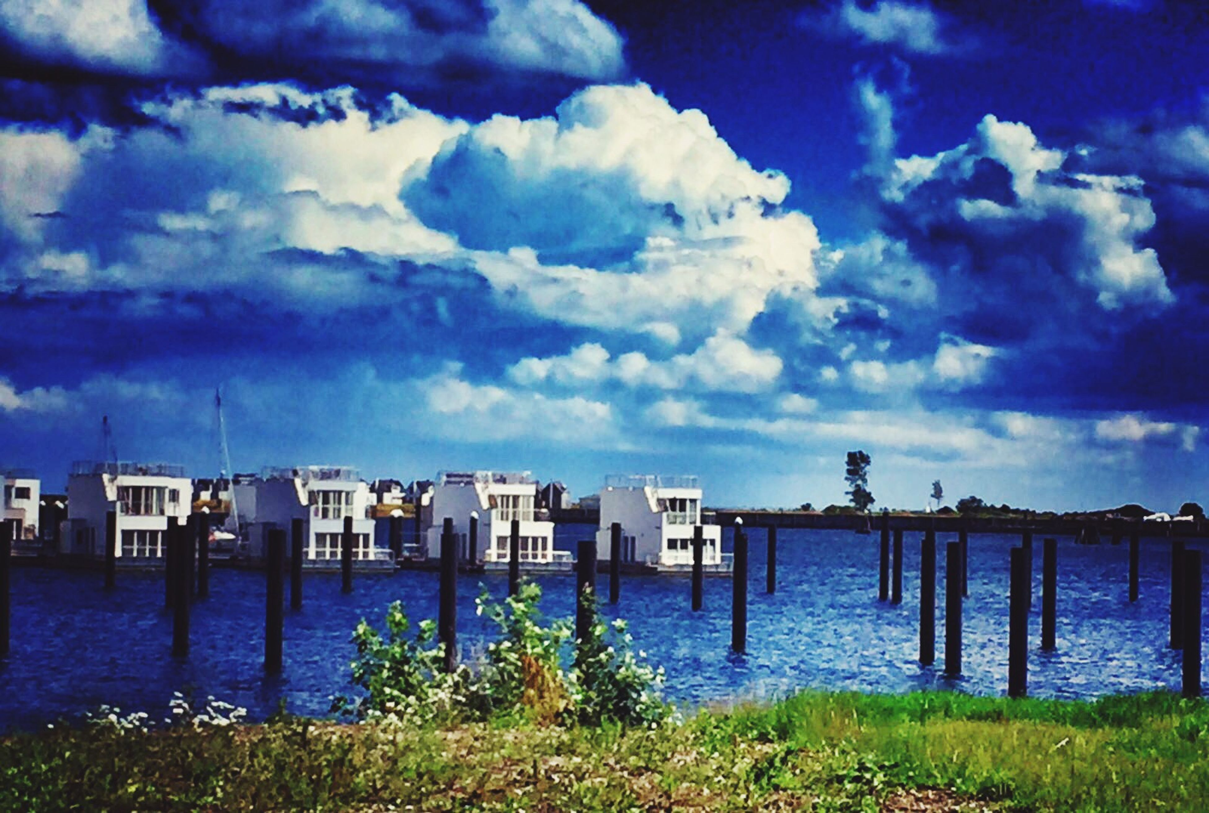 sky, water, cloud - sky, built structure, river, architecture, blue, cloudscape, plant, day, riverbank, outdoors, nature, tranquility, scenics, tranquil scene, cloudy, no people, dramatic sky, beauty in nature, cumulus cloud