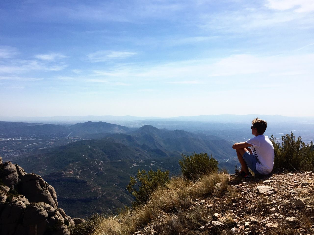 real people, nature, sitting, one person, sky, leisure activity, casual clothing, beauty in nature, mountain, full length, tranquil scene, tranquility, backpack, lifestyles, day, outdoors, scenics, men, photographing, relaxation, adventure, vacations, tree, technology, young adult, adult, people