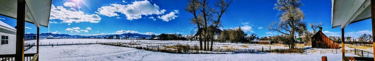 snow, winter, cold temperature, sky, mountain, nature, scenics, cloud - sky, tree, landscape, tranquil scene, weather, frozen, beauty in nature, panoramic, outdoors, blue, day, tranquility, mountain range, sunlight, no people, travel destinations, building exterior, bare tree, snowing, architecture, ski lift, city