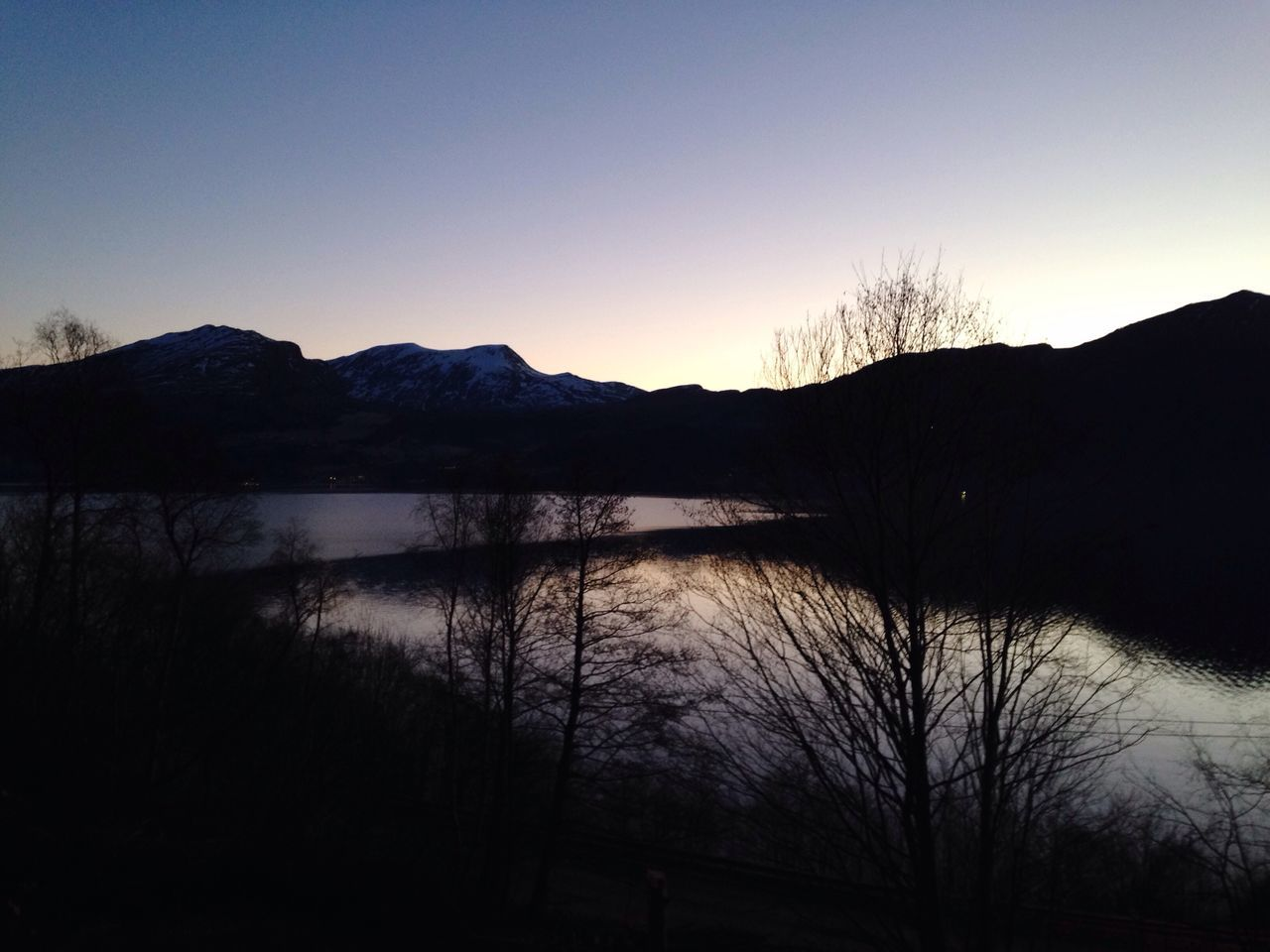 silhouette, scenics, mountain, nature, tranquil scene, tranquility, sunset, lake, beauty in nature, water, no people, reflection, mountain range, outdoors, sky, tree, landscape, travel destinations, bare tree, clear sky, day