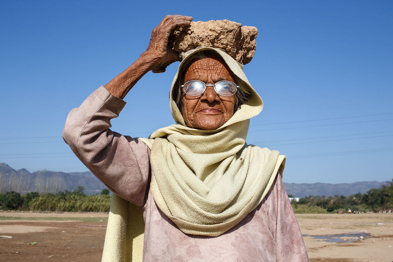 A woman with a rock on top of her head in the outskirts of Anadpur Sahib, the holy town of Sikkhism in the state of Punjab in India. I wonder where she was taking it. India Old Woman One Person Outdoors Portrait Portrait Of A Woman Punjab The Portraitist - 2017 EyeEm Awards