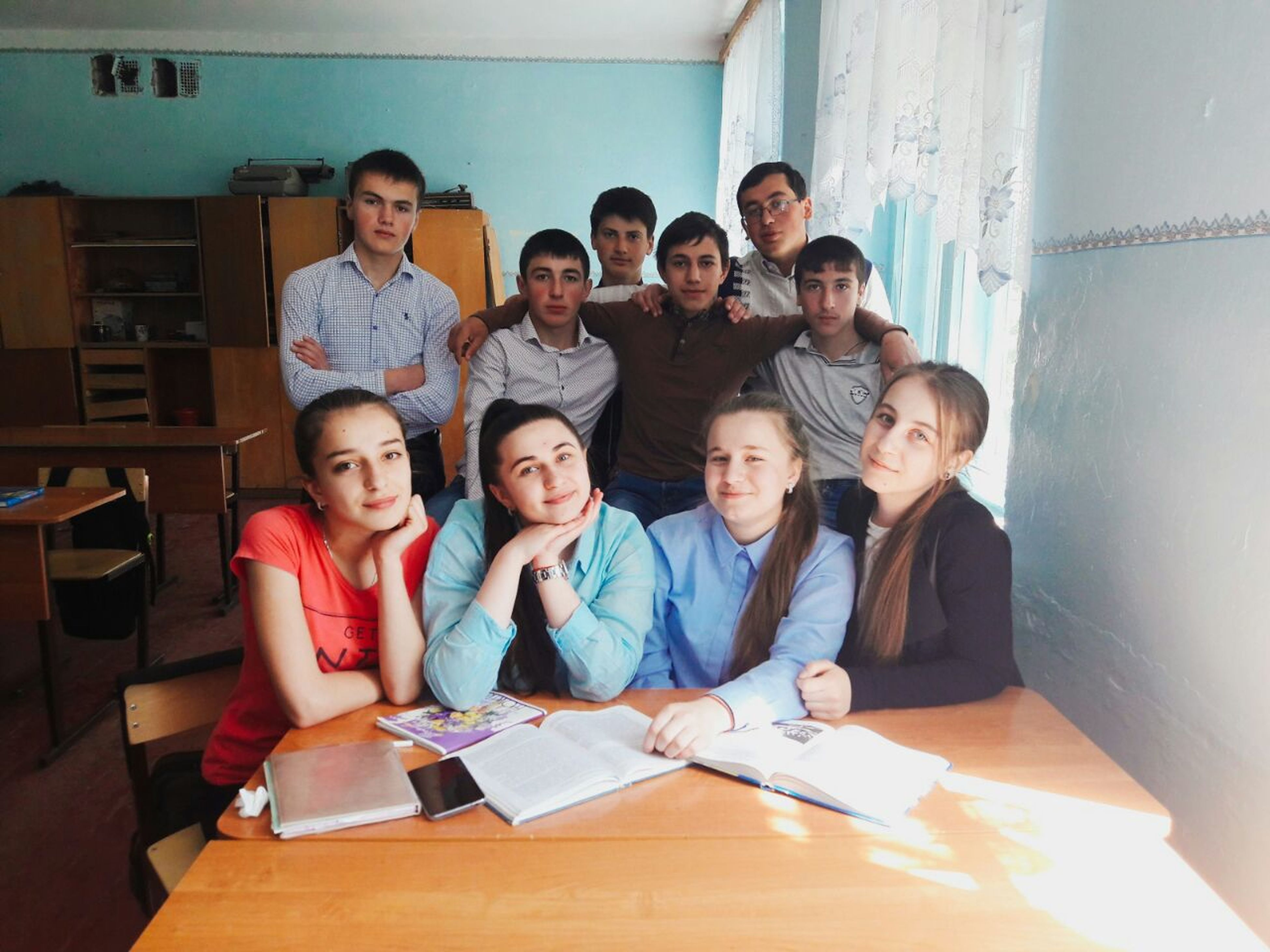 looking at camera, child, sitting, girls, portrait, boys, togetherness, young women, indoors, young adult, classroom, people, men, education, learning, teamwork, student, women, smiling, occupation, adult, cooperation, day