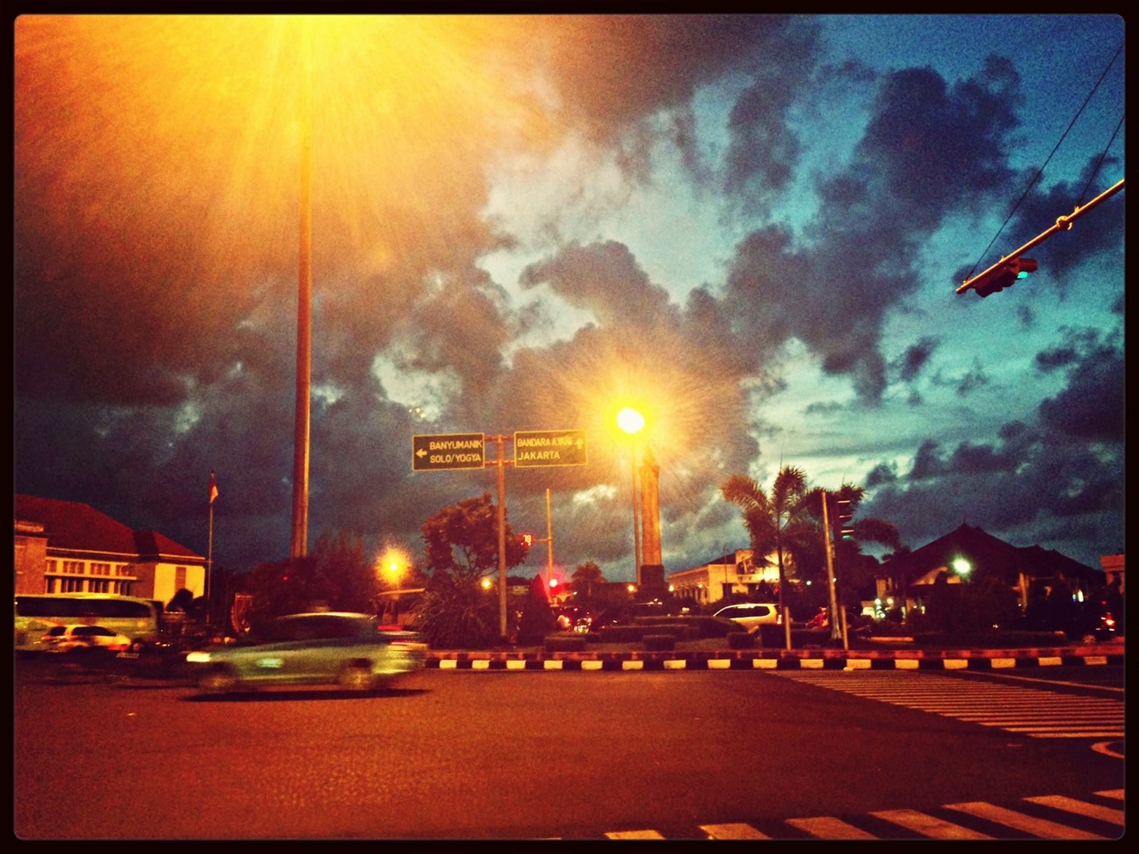 illuminated, transfer print, night, sky, auto post production filter, street light, building exterior, architecture, built structure, lighting equipment, city, cloud - sky, dusk, street, outdoors, light - natural phenomenon, transportation, no people, road, cloudy