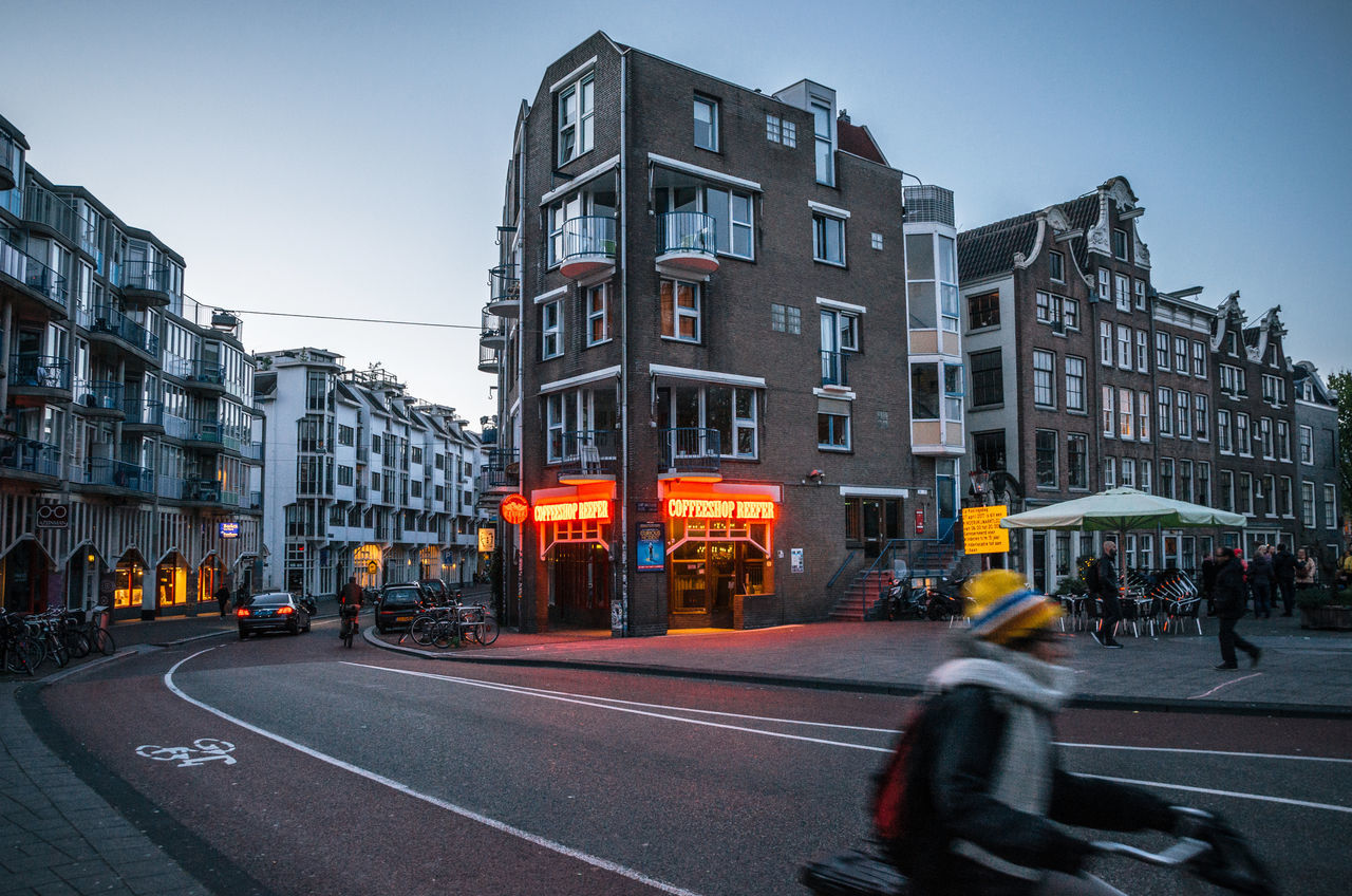 Adult rides a bicycle in historical part of Amsterdam with typical traditional houses against The Coffeeshop Reefer with legal soft drugs in evening. Amsterdam Architecture Building Exterior Built Structure City Coffeeshop Drugs Dutch Evening Holland Motion Netherlands Night Lights Outdoors