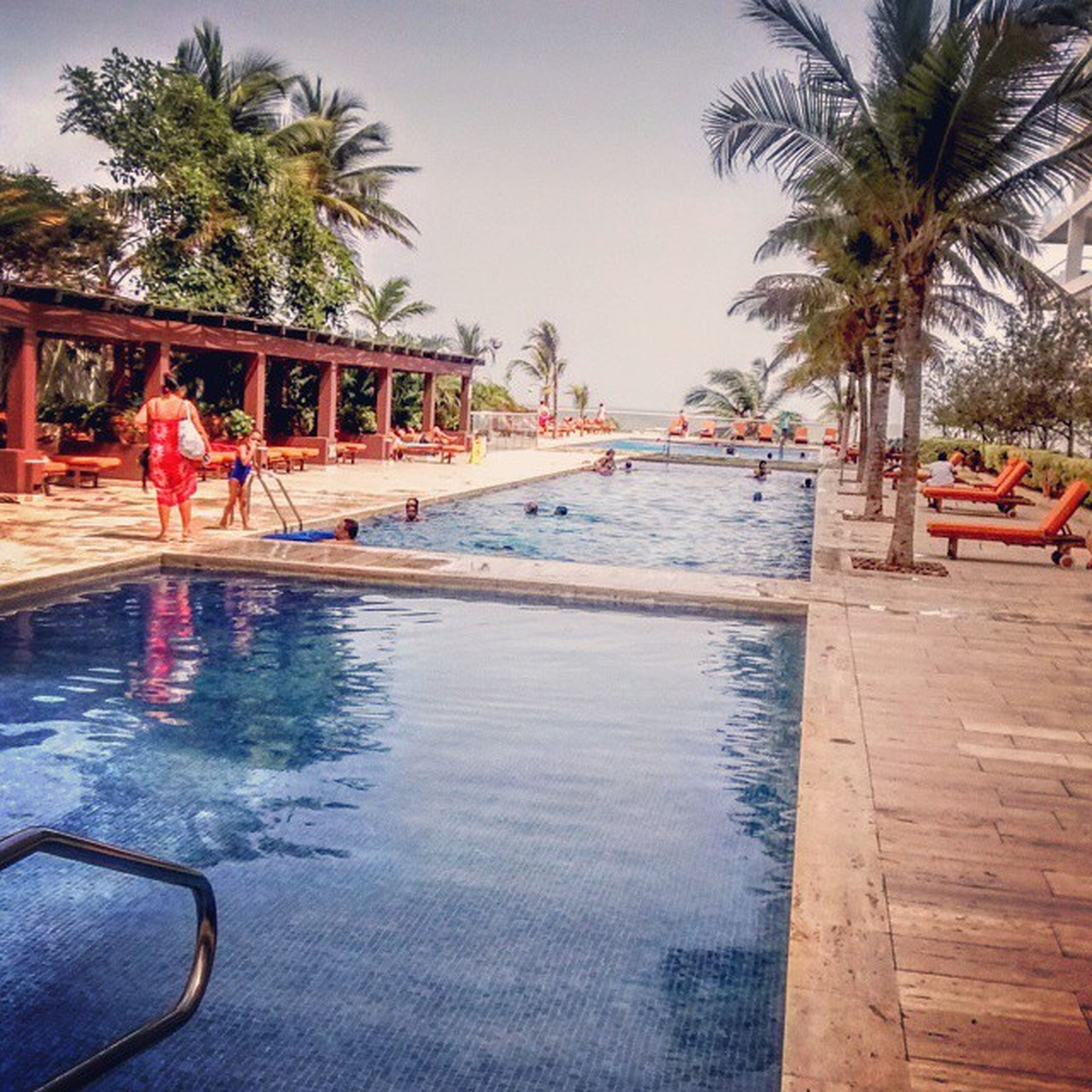 water, lifestyles, leisure activity, palm tree, tree, swimming pool, beach, sea, clear sky, people, built structure, enjoyment, vacations, architecture, railing, tourist, full length