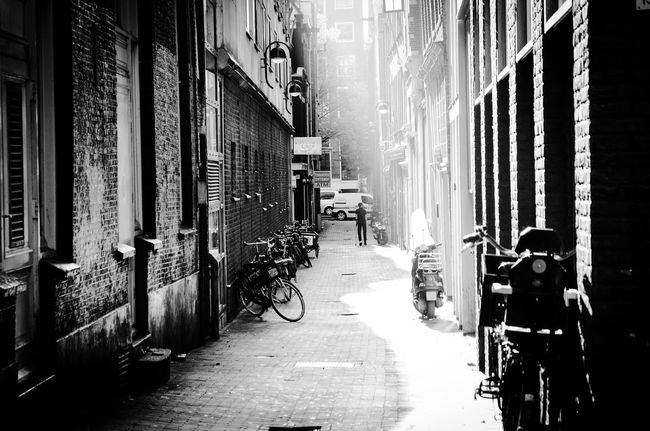 Architecture Building Exterior Built Structure City Street The Way Forward Residential Structure Land Vehicle Diminishing Perspective Mode Of Transport Narrow Office Building Alley Stationary Building Story Bycicle Light And Shadow Silhouette