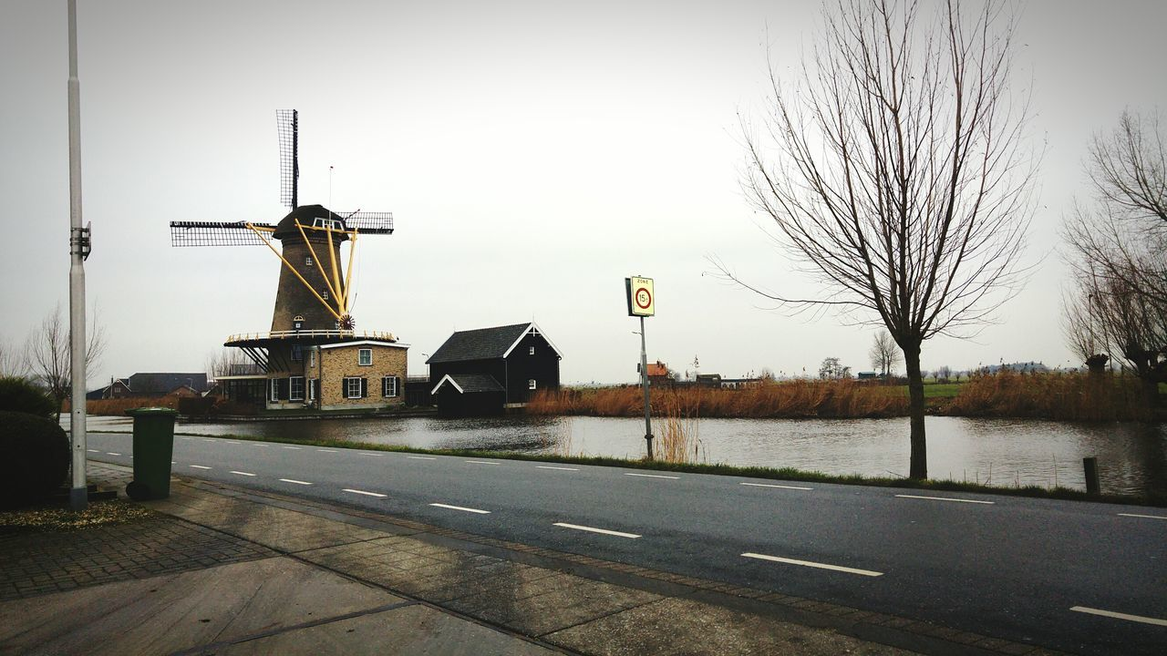 transportation, road, water, no people, bare tree, sky, outdoors, architecture, built structure, day, clear sky, nature, building exterior, windmill, tree