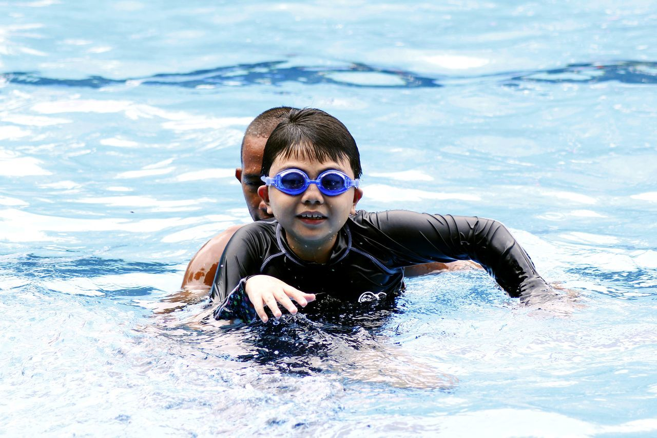 a young child learns how to swim with the help of a swimming coach Action Boy Child Coach Exercise Kid Learn Male Pool Sport Swim Swimmer Swimming Teacher Water Wet Young Youth