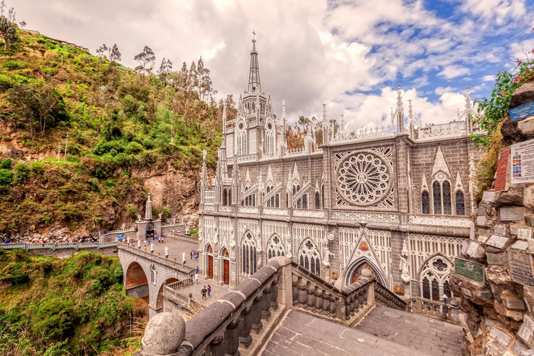 Las Lajas Colombian Catholic Church, Built Between 1916 And 1948 Is A Popular Destination For Religious Believers From All Part Of Latin America Andes Arch Architecture Bridge - Man Made Structure Built Structure Cathedral Catholic Church City Cityscape Cloud - Sky Colombia Day Huge Las Lajas Cathedral Mountain No People Outdoor Outdoors Sky Sky And Clouds South America Travel Destinations Tree Vacations