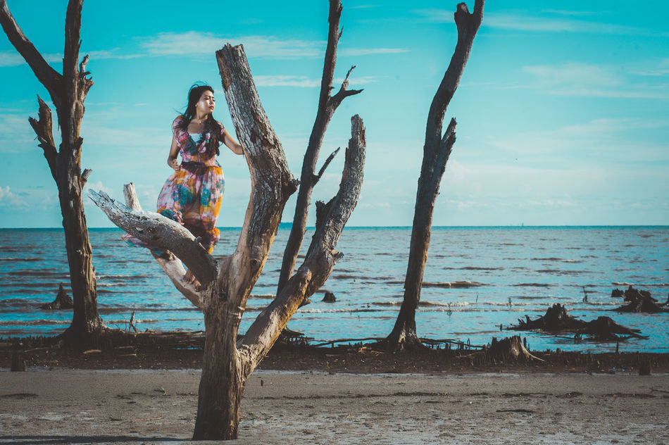 Beach Beauty In Nature Day Full Length Horizon Over Water Leisure Activity Lifestyles Nature One Person Outdoors Real People Scenics Sea Sky Tree Tree Trunk Water Young Adult Young Women