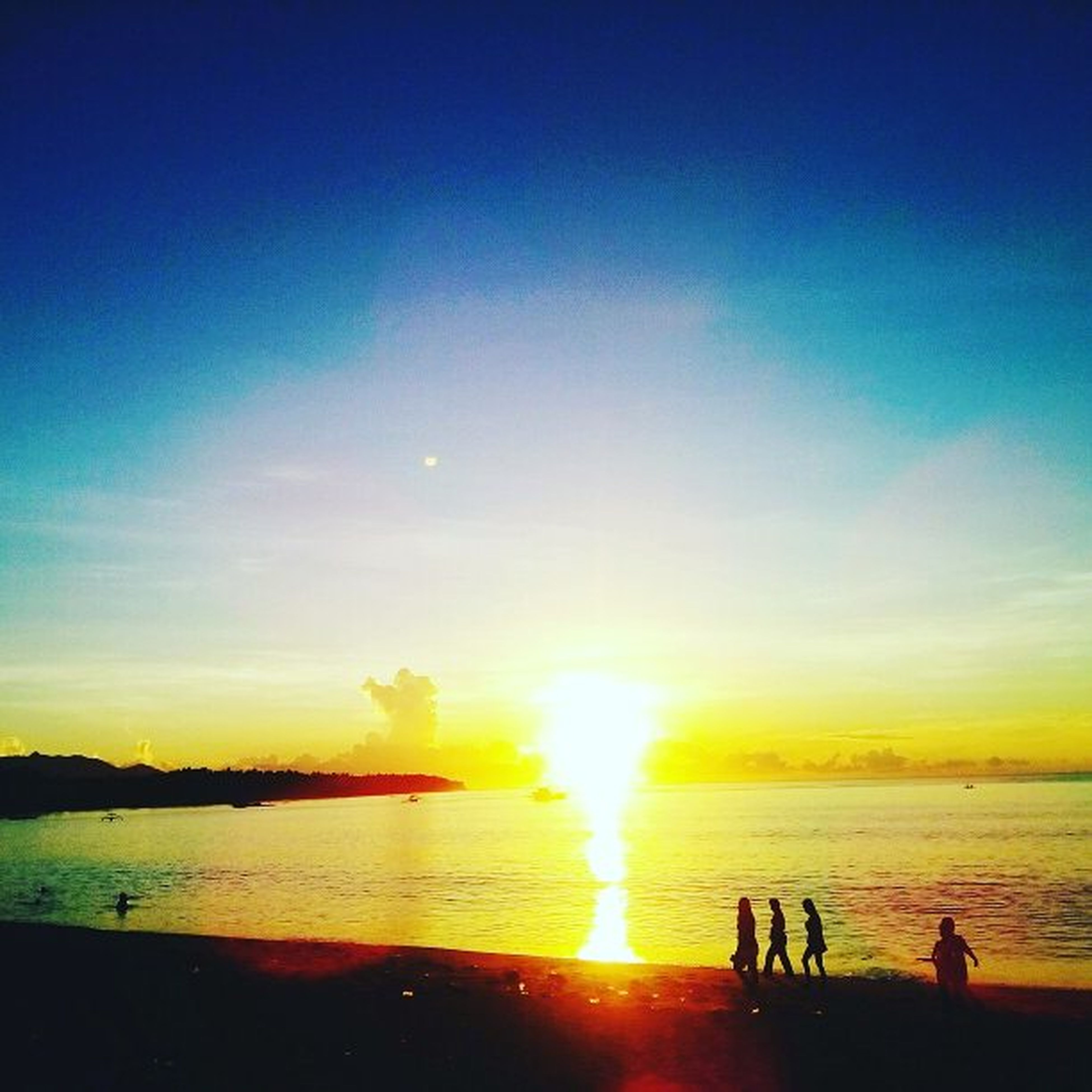 sunset, silhouette, sea, water, real people, leisure activity, beauty in nature, sky, nature, beach, men, lifestyles, scenics, vacations, sun, horizon over water, sunlight, outdoors, women, weekend activities, togetherness, enjoyment, wave, large group of people, day, people, adult