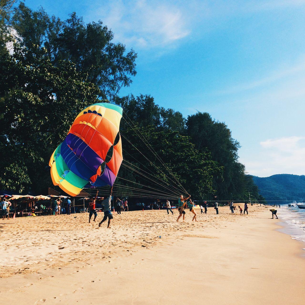 Parasailing On Beach Against Sky