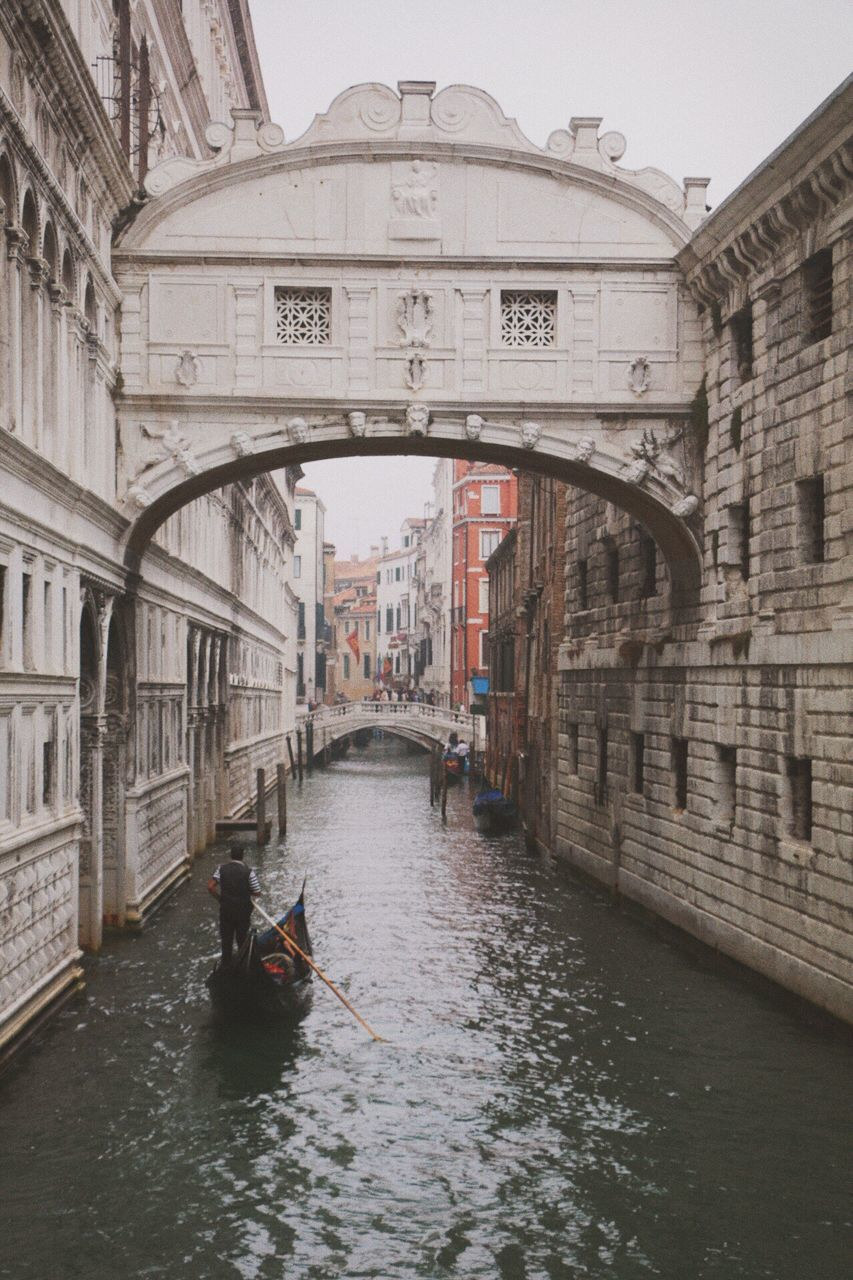 architecture, canal, transportation, gondolier, gondola - traditional boat, arch, built structure, nautical vessel, building exterior, one person, day, real people, gondola, oar, bridge - man made structure, outdoors, travel destinations, men, water, rowing, people