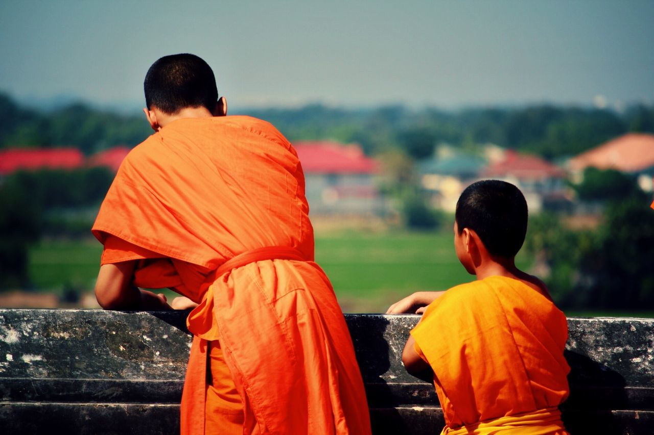 Rear View Real People Orange Color Focus On Foreground Lifestyles Two People Leisure Activity Traditional Clothing Boys Men Outdoors Religion Standing Women Togetherness Sky Day Buddhist Monks Ayuthaya Thailand